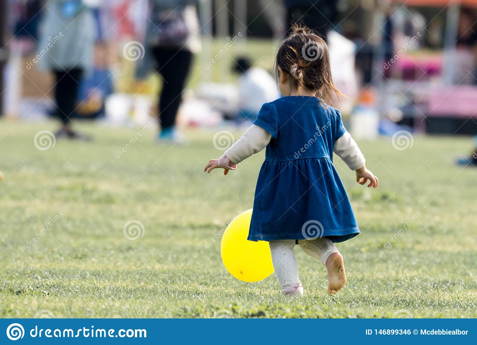 Uma menina nova que persegue um balão amarelo e para jogar com ele no parque