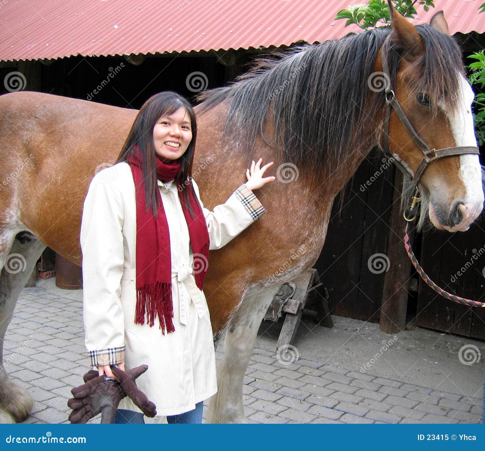 Uma menina ou uma mulher com um cavalo