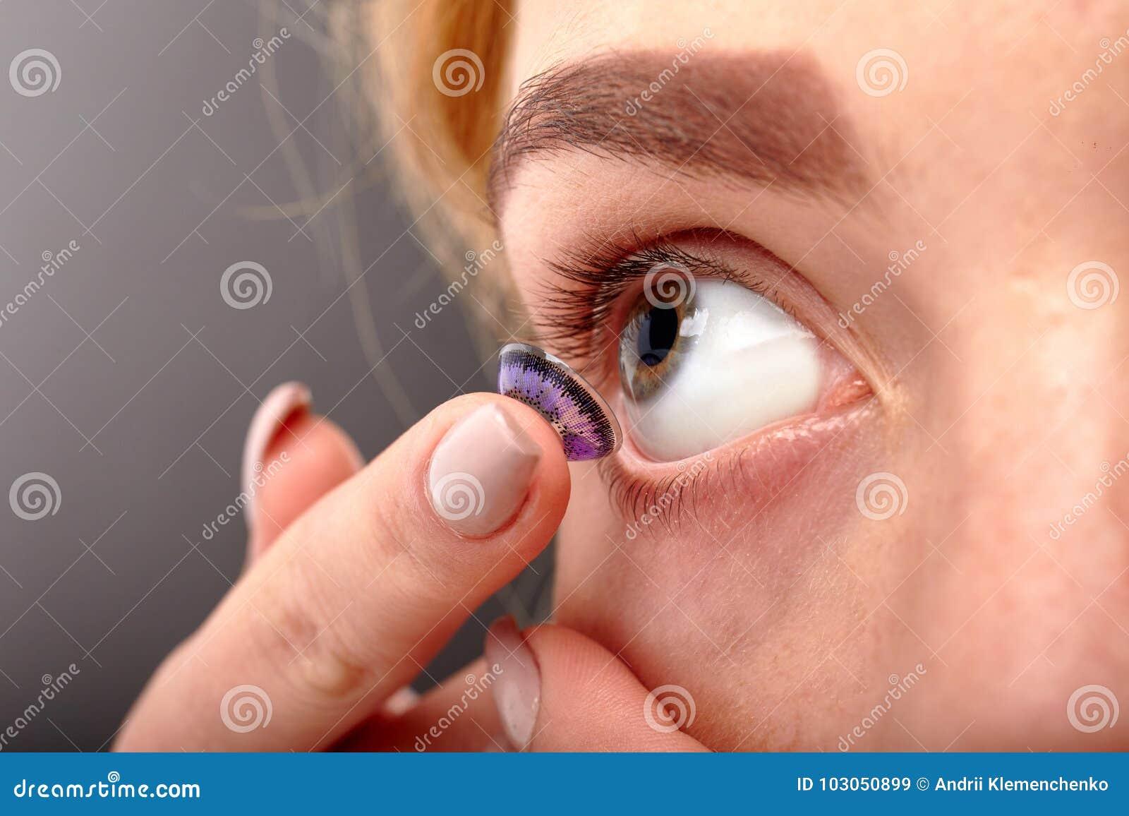 Uma menina põe-se em uma lente de close-up