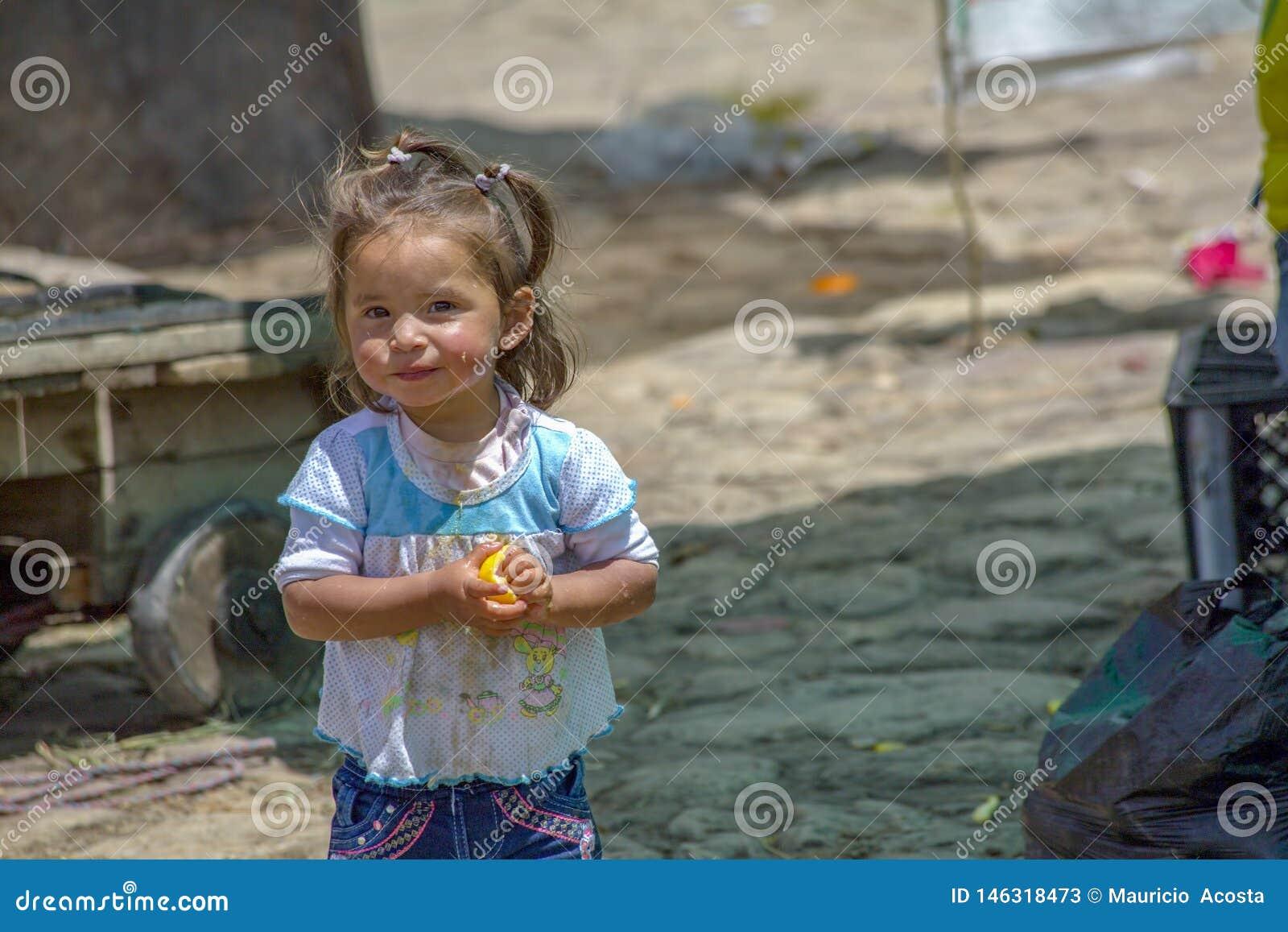 Uma menina que come uma laranja
