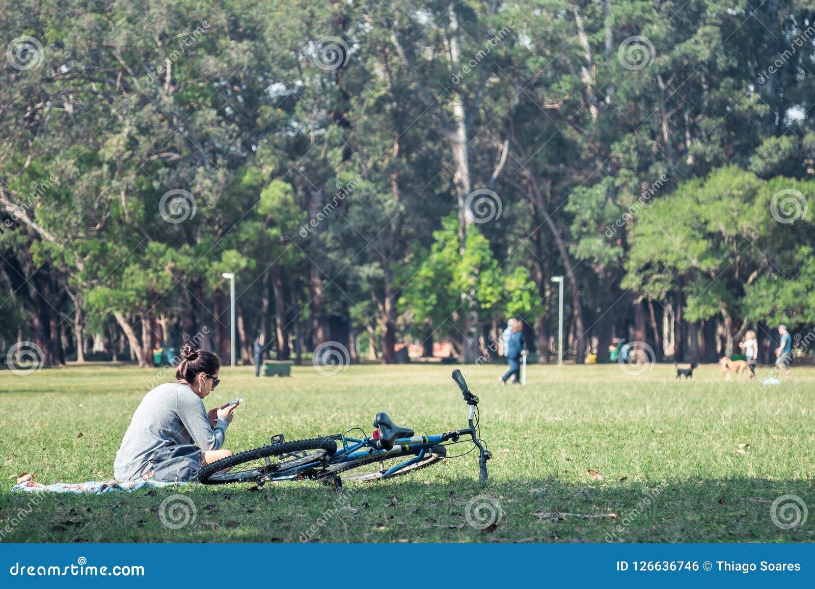 Uma menina que escuta a música em um campo de grama