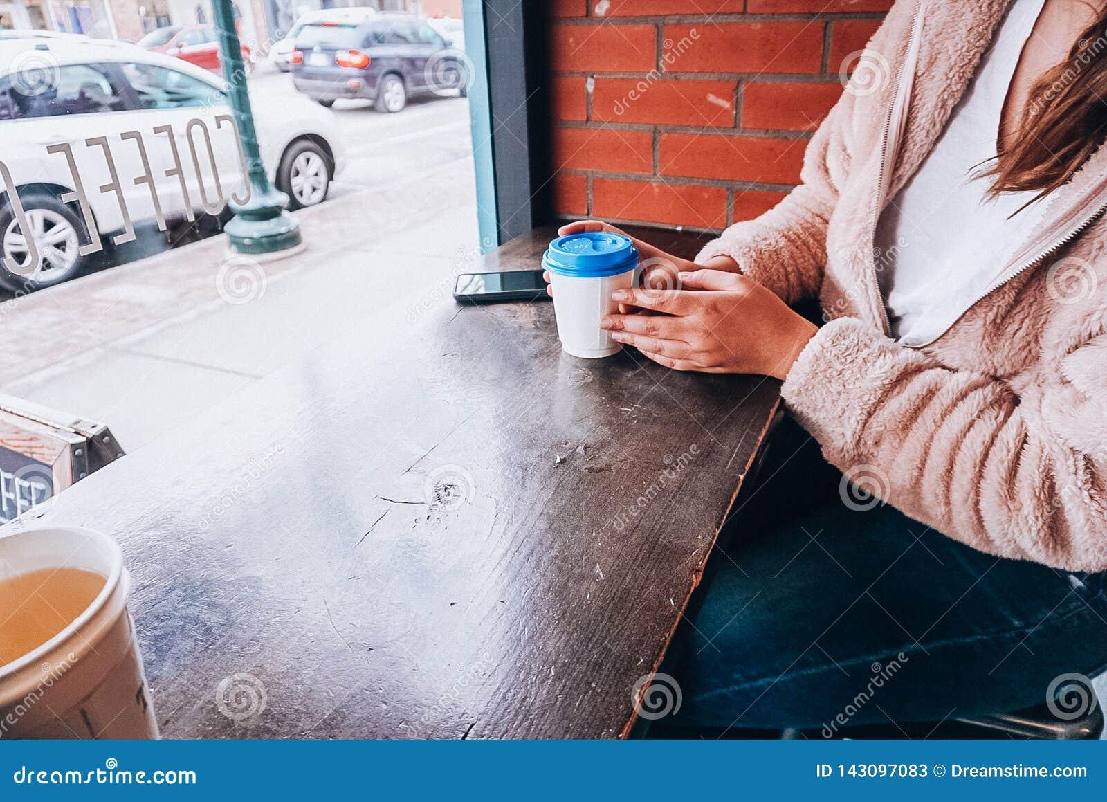 Uma menina que guarda uma xícara de café com uma tampa azul