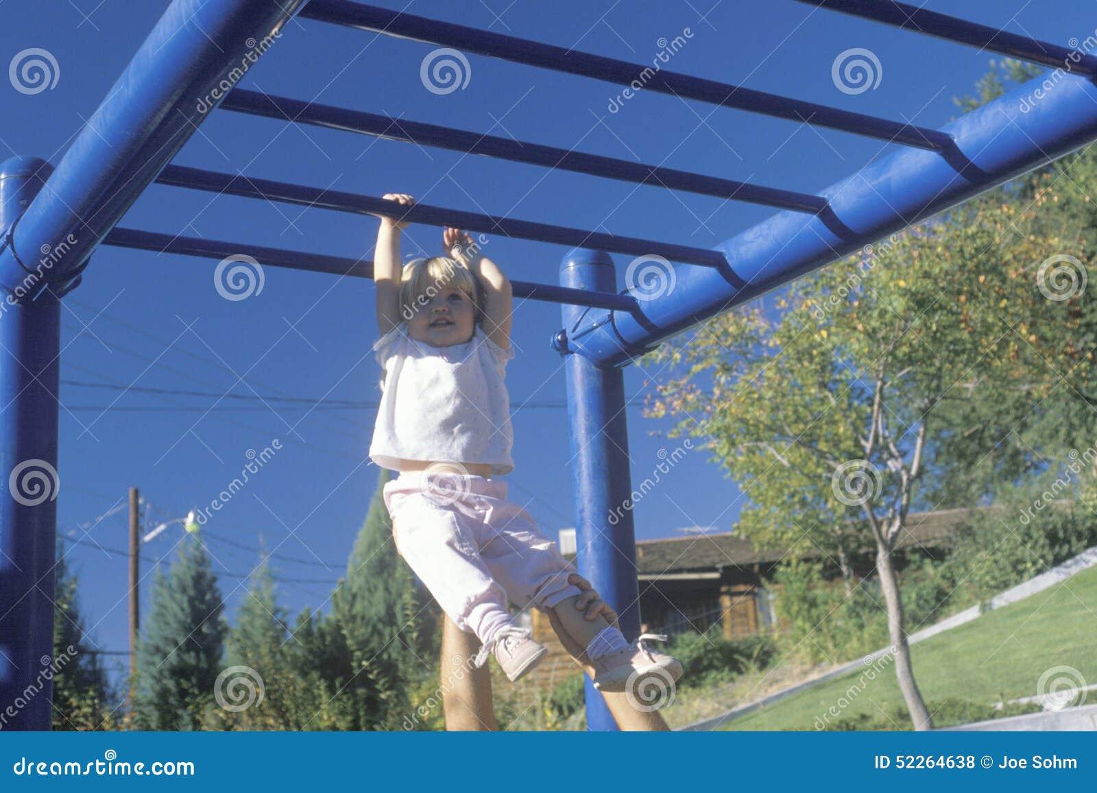 Uma menina que joga no gym de selva, nanômetro
