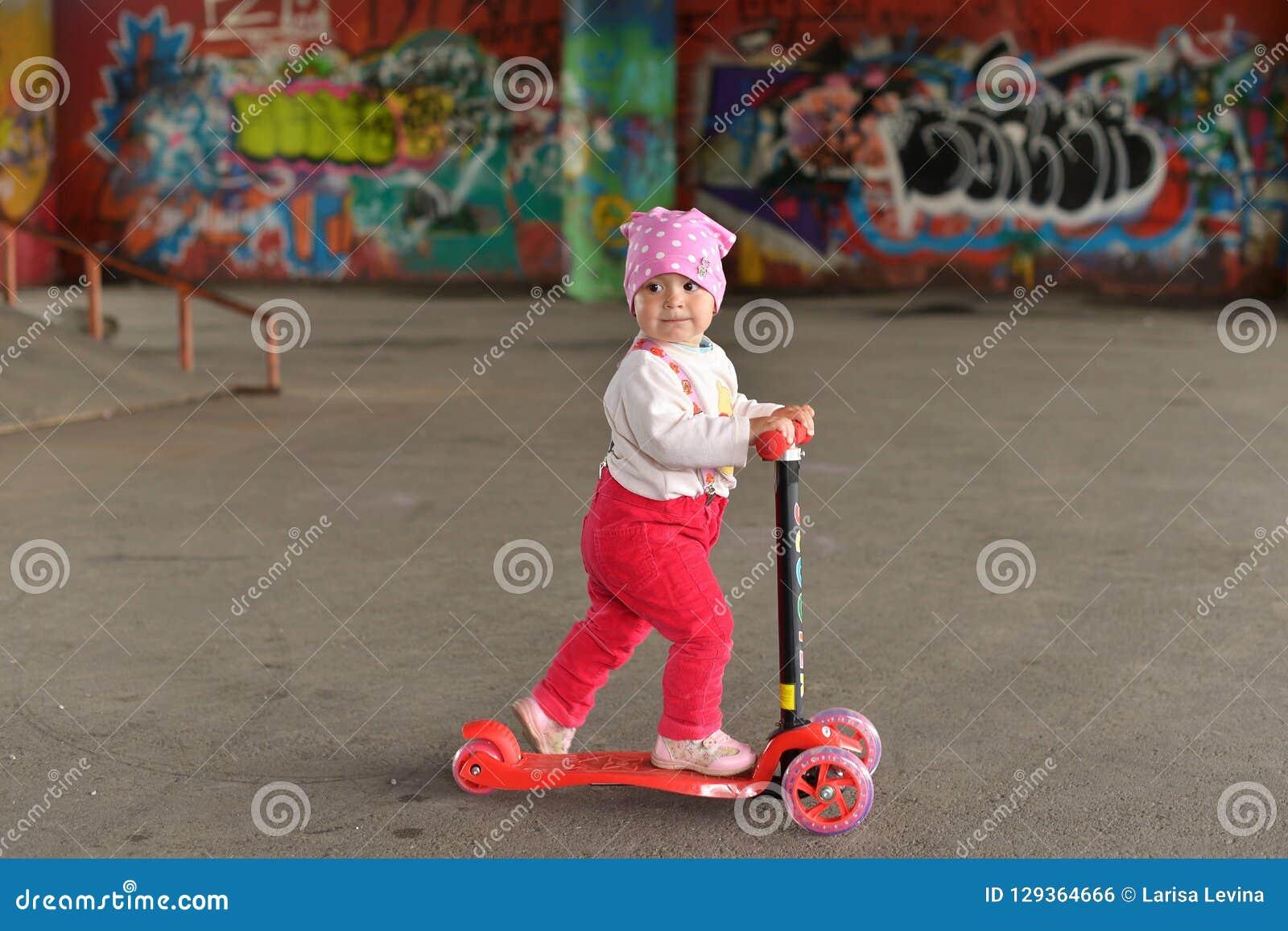 Uma menina que monta um  trotinette  do ` s das crianças em um parque do patim