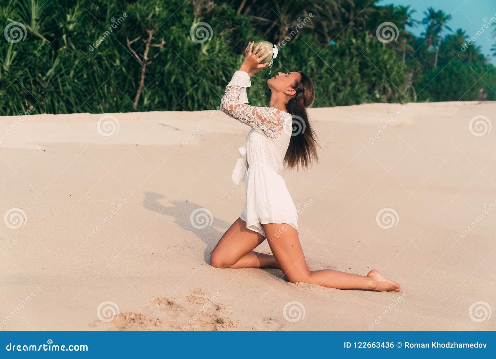 Uma menina  sexy  ajoelha-se em um Sandy Beach branco na perspectiva da selva, vestida em um fato-macaco à moda, aumentou a