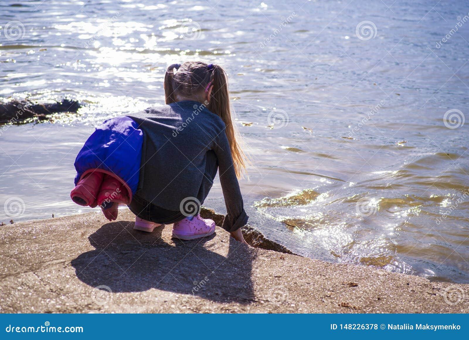 Uma menina toca no rio com sua mão Uma menina pelo rio em um dia ensolarado