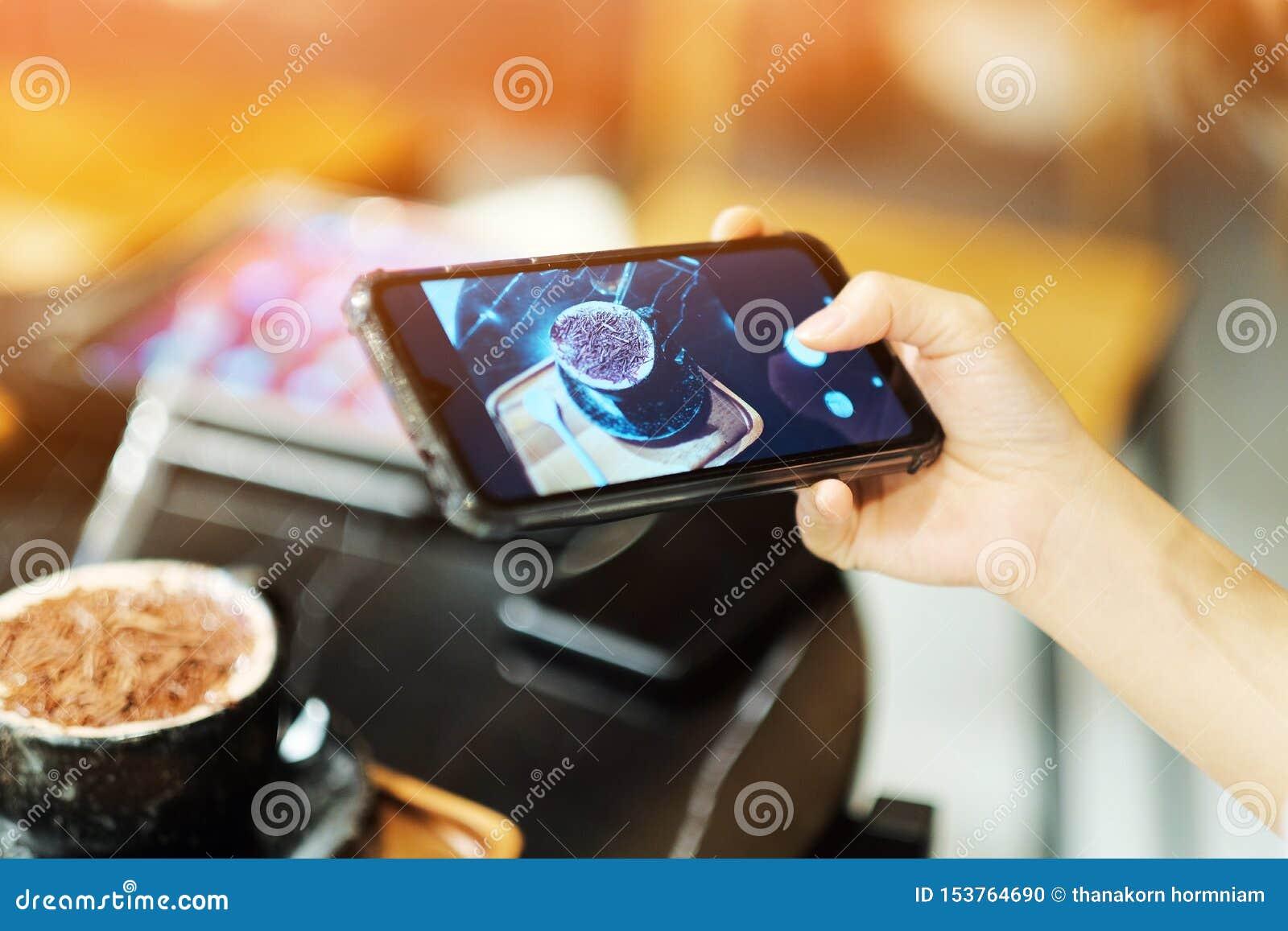 Uma menina usou seu smartphone para a tomada uma imagem no café do café