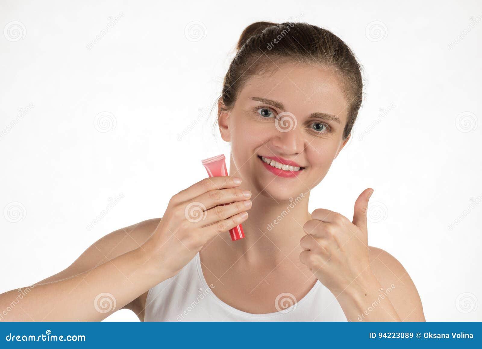 Uma moça bonita aplica um batom vermelho líquido persistente