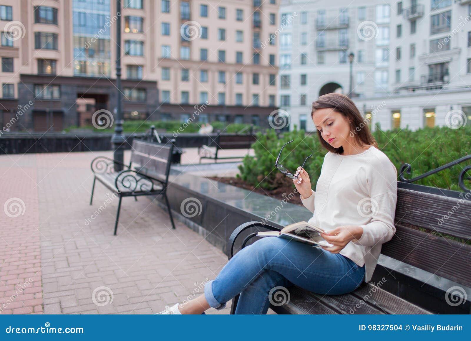Uma moça bonita com o cabelo marrom longo que senta-se em um banco com um livro, guardando monóculos Saiu da casa em um eveni mor