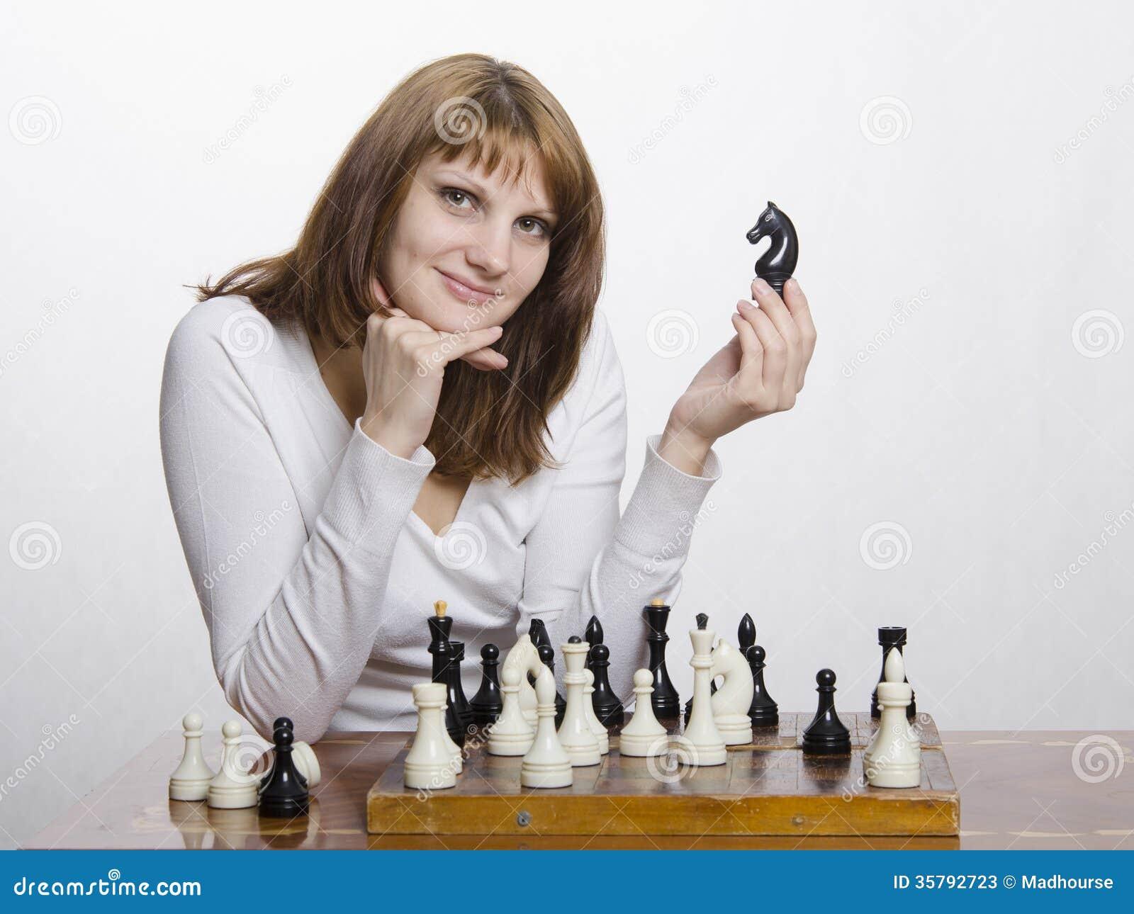 Uma moça com uma figura de um cavalo, na placa de xadrez