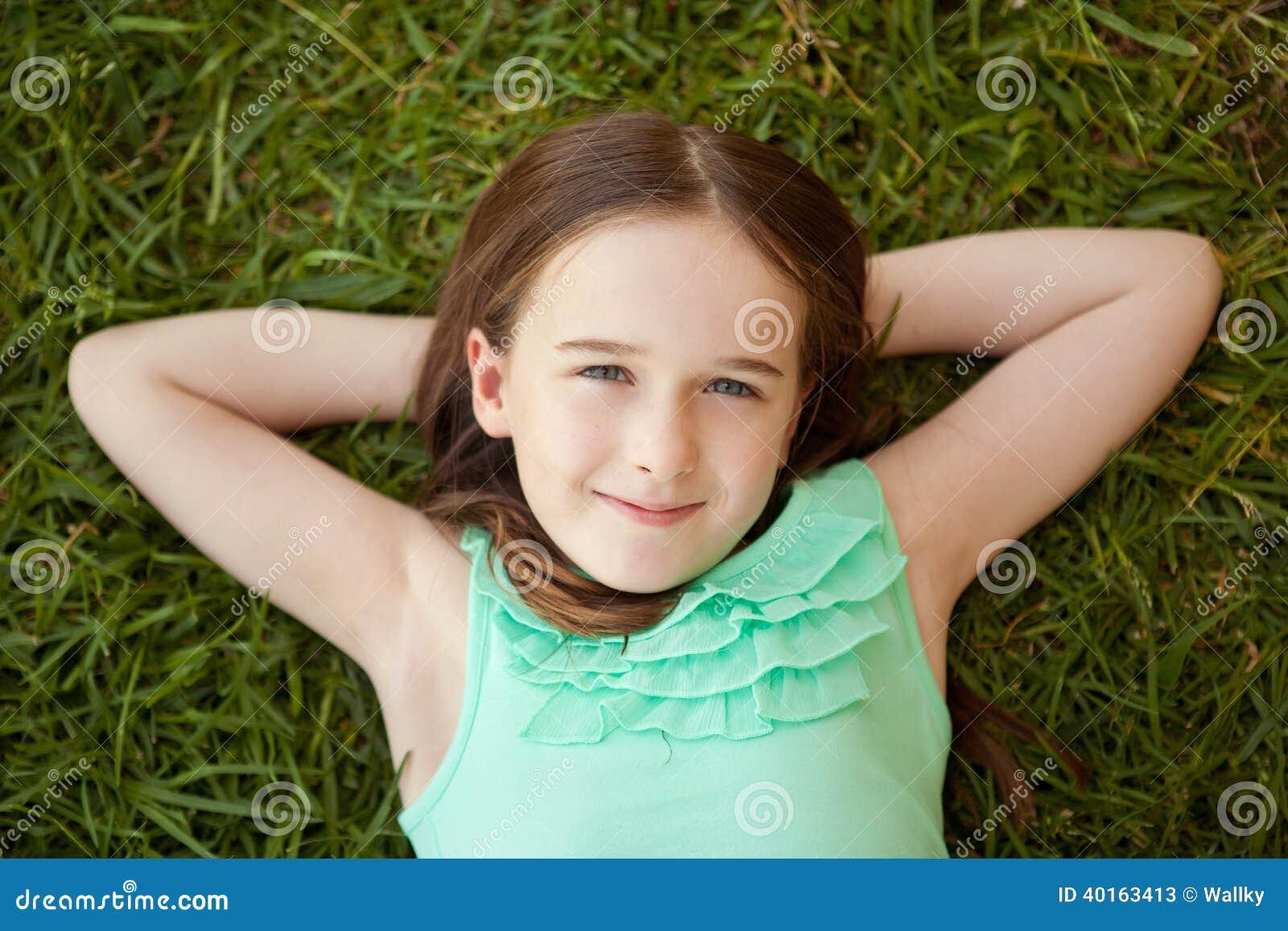 Uma moça está encontrando-se nela para trás na grama que olha acima