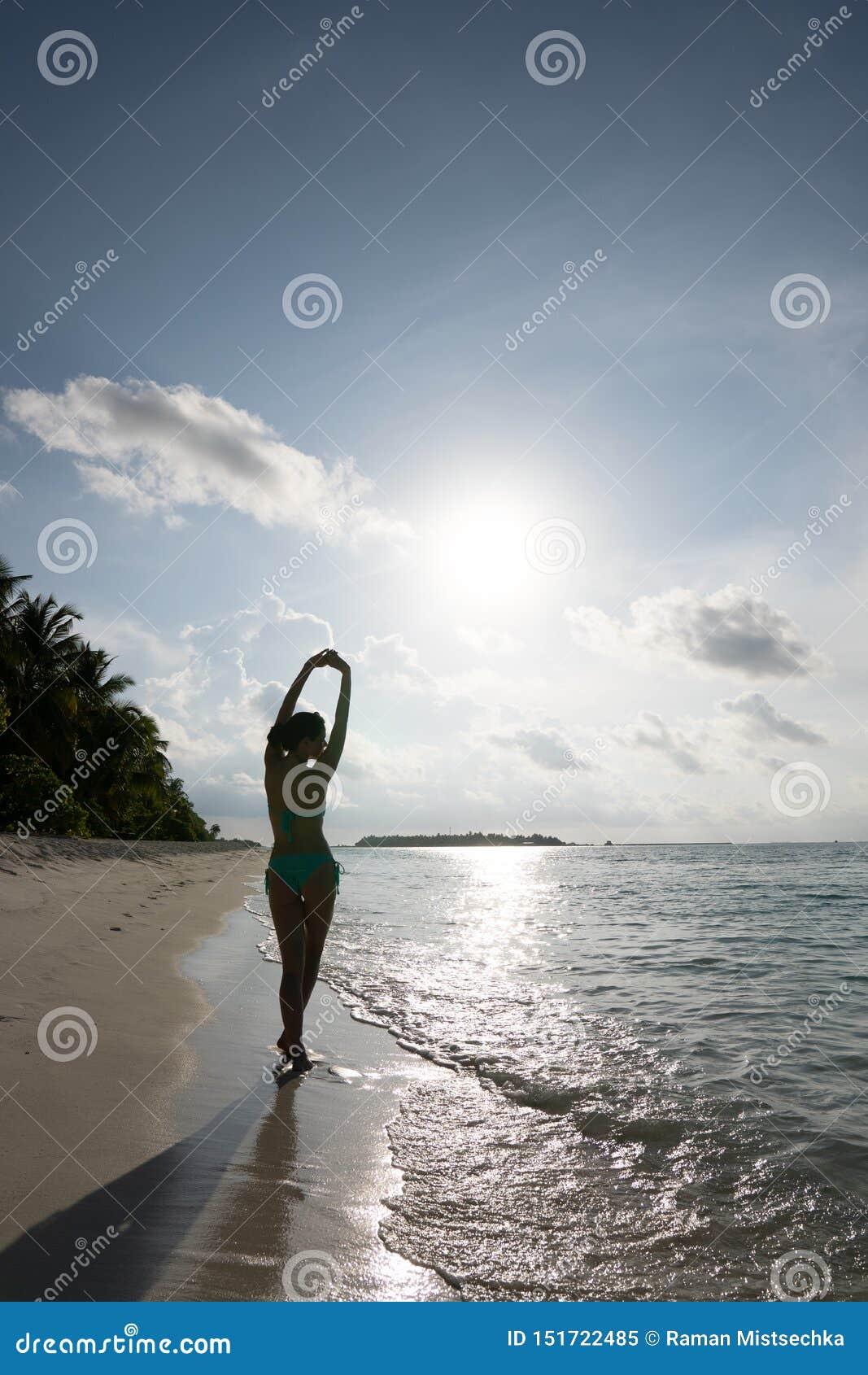 Uma moça está estando belamente em um maiô na borda da água e está tomando sol no sol