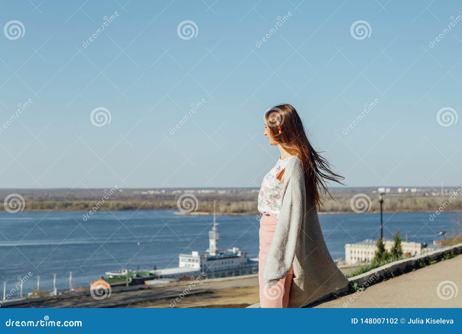Uma moça na terraplenagem de um grande rio, olhando a água