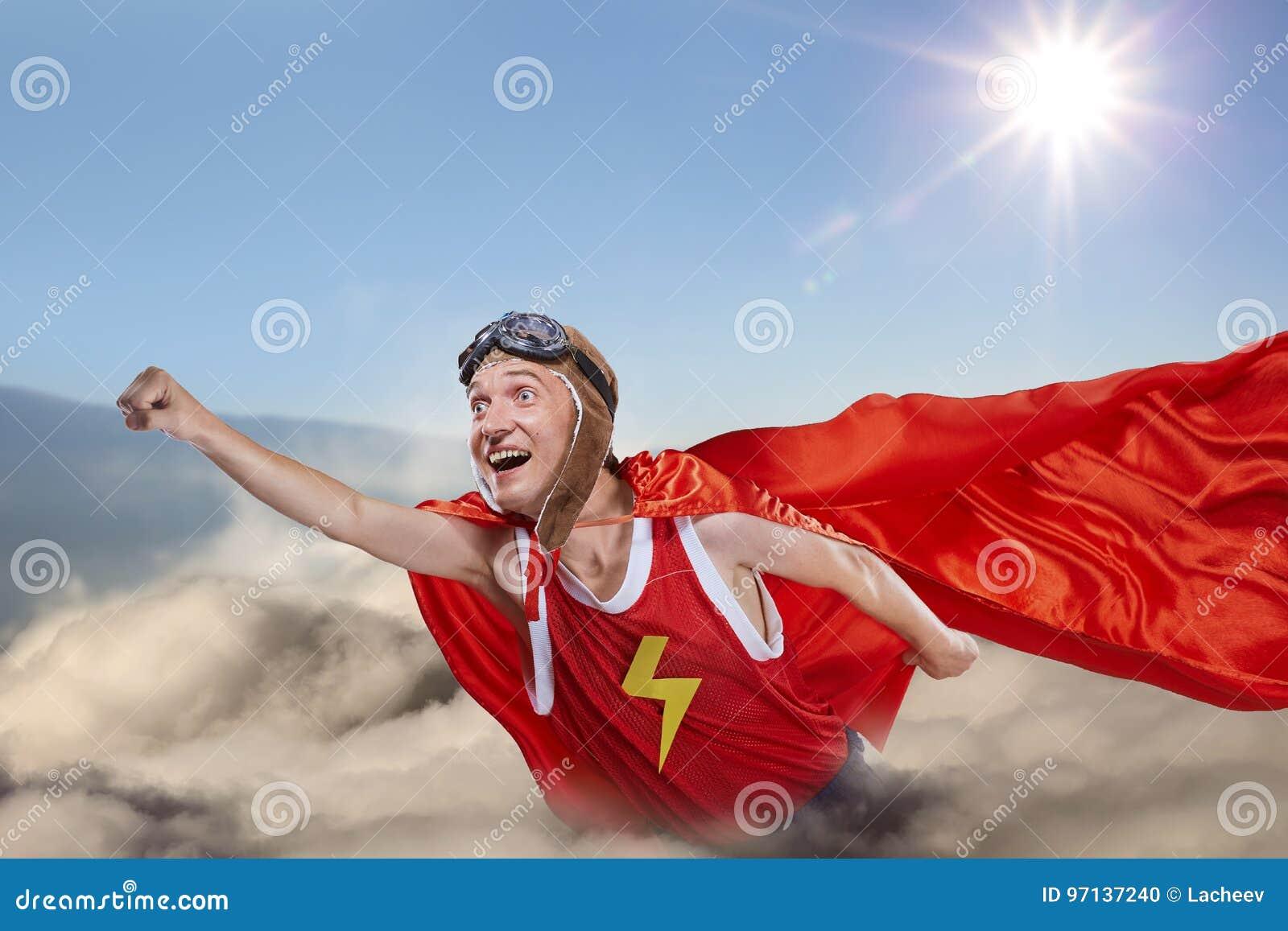 Uma mosca engraçada do super-herói acima das nuvens no céu