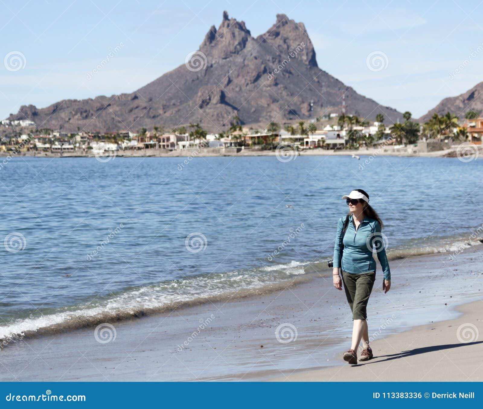 Uma mulher anda a praia, montanha de Tetakawi atrás, San Carlos, M