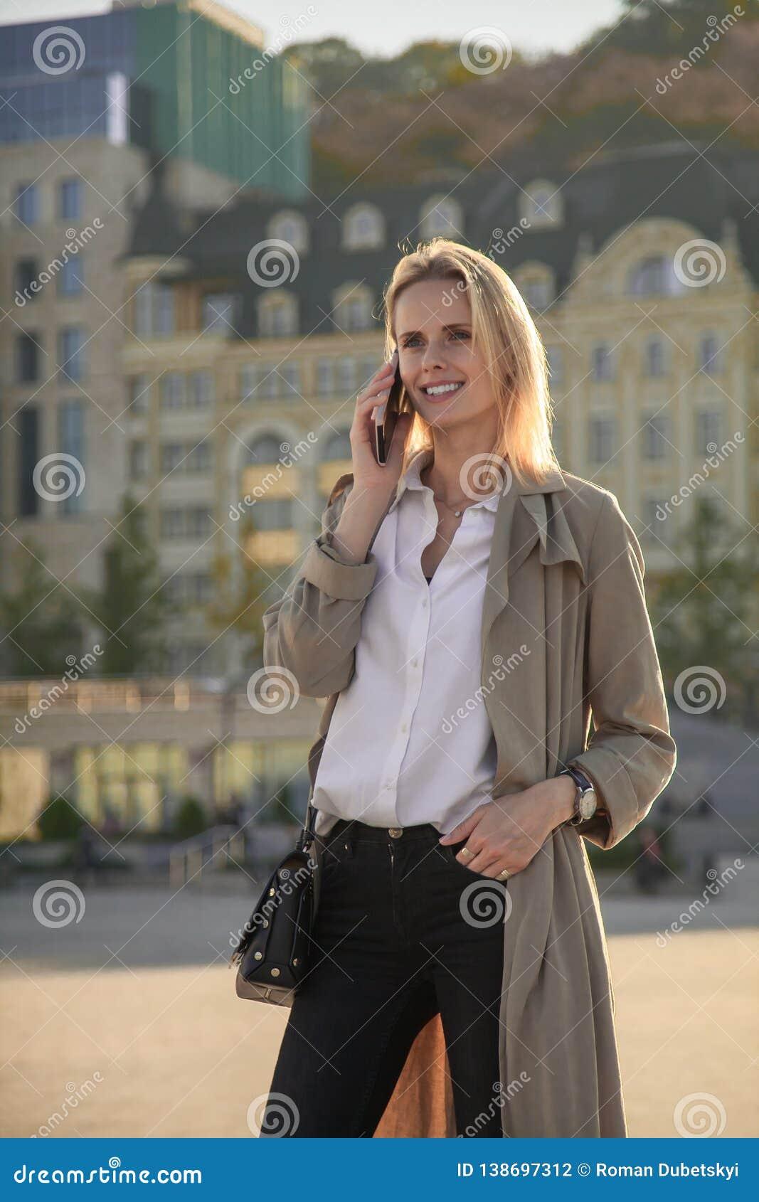 Uma mulher bem sucedida nova em um revestimento de trincheira, andando na rua, falando por seu telefone celular