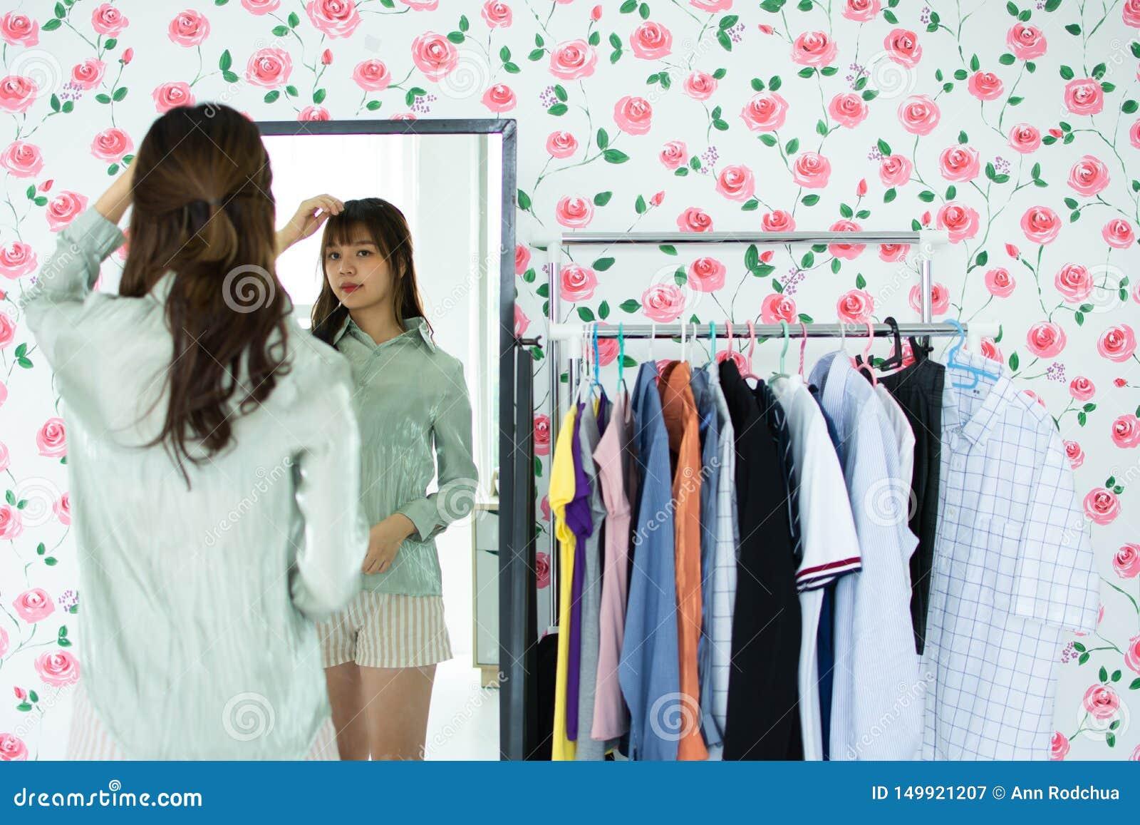 Uma mulher bonito está olhando o mirrow em sua sala