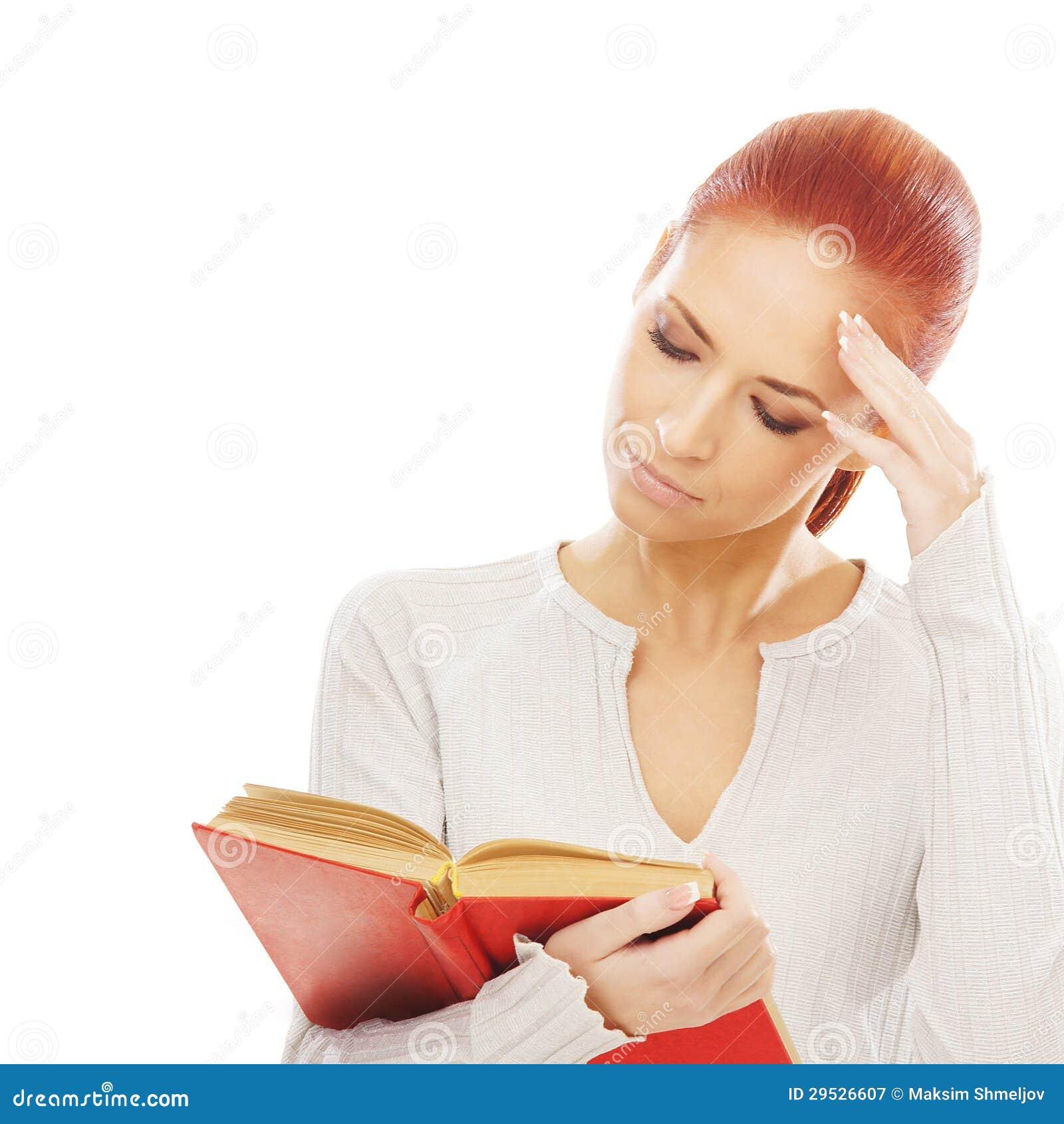 Uma mulher caucasiano do redhead novo que lê um livro