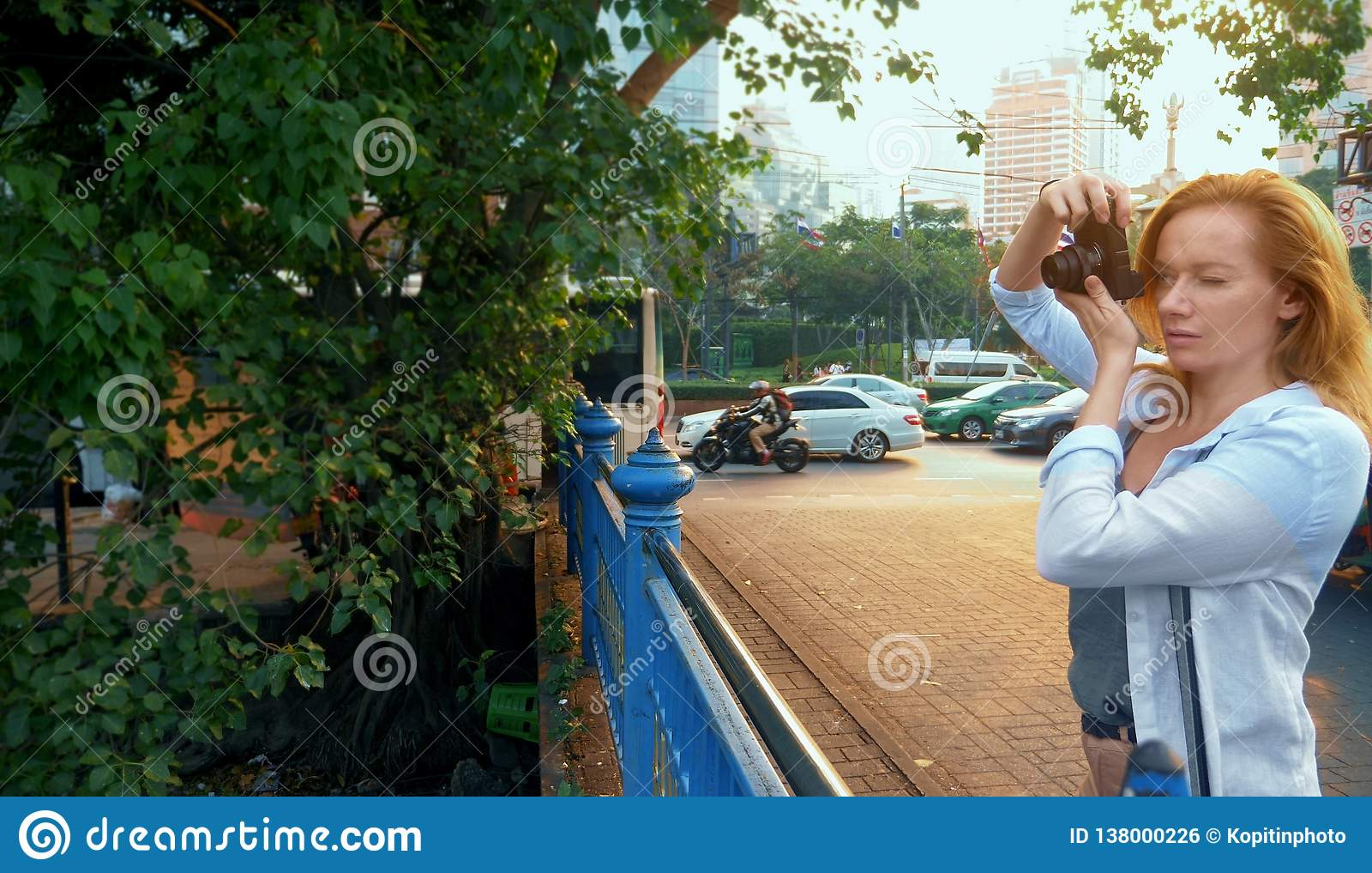 Uma mulher com uma câmera anda através das ruas de uma grande cidade moderna