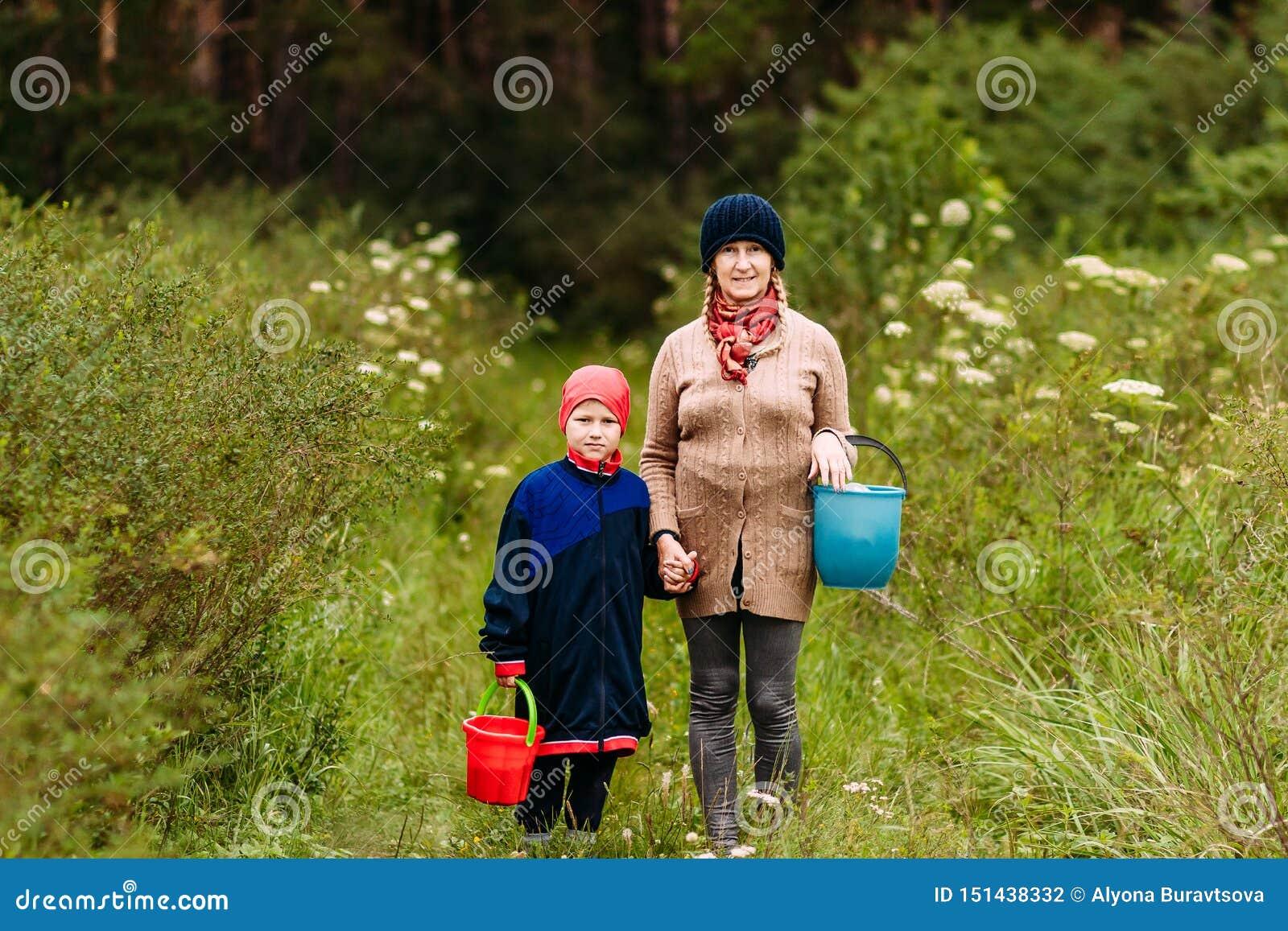 Uma mulher da idade da reforma e um menino de sete anos nas madeiras com as cubetas dos cogumelos