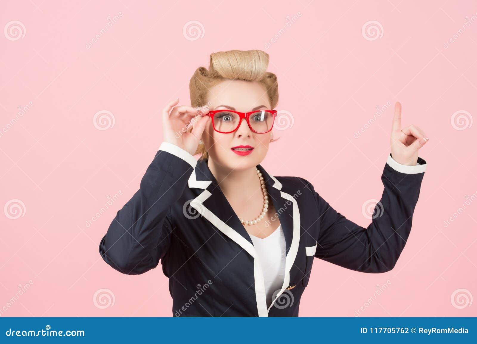 Uma mulher de negócios em vidros vermelhos aponta acima no fundo cor-de-rosa A senhora no revestimento que consideram a propagand