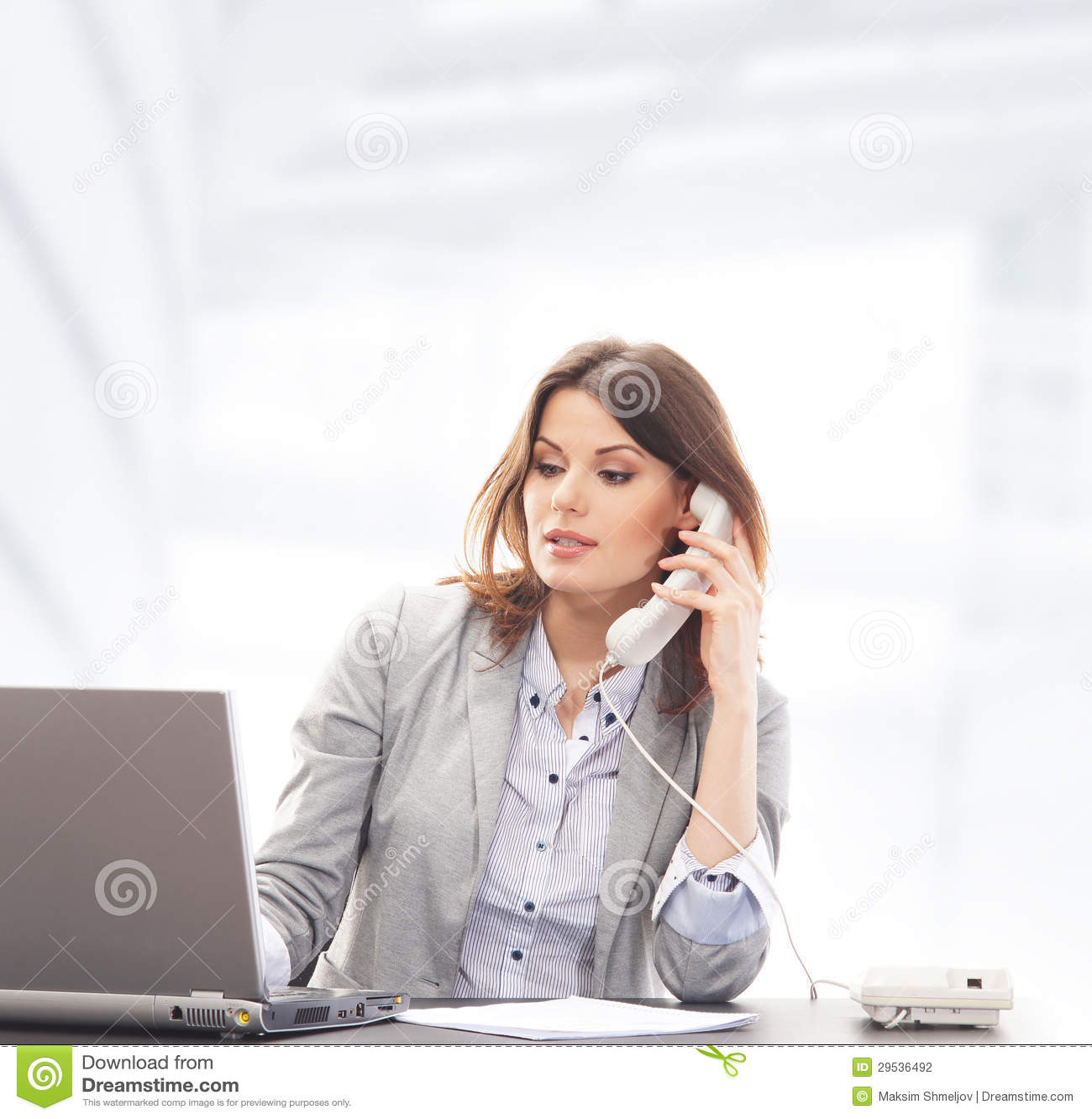 Uma mulher de negócios na roupa formal no telefone