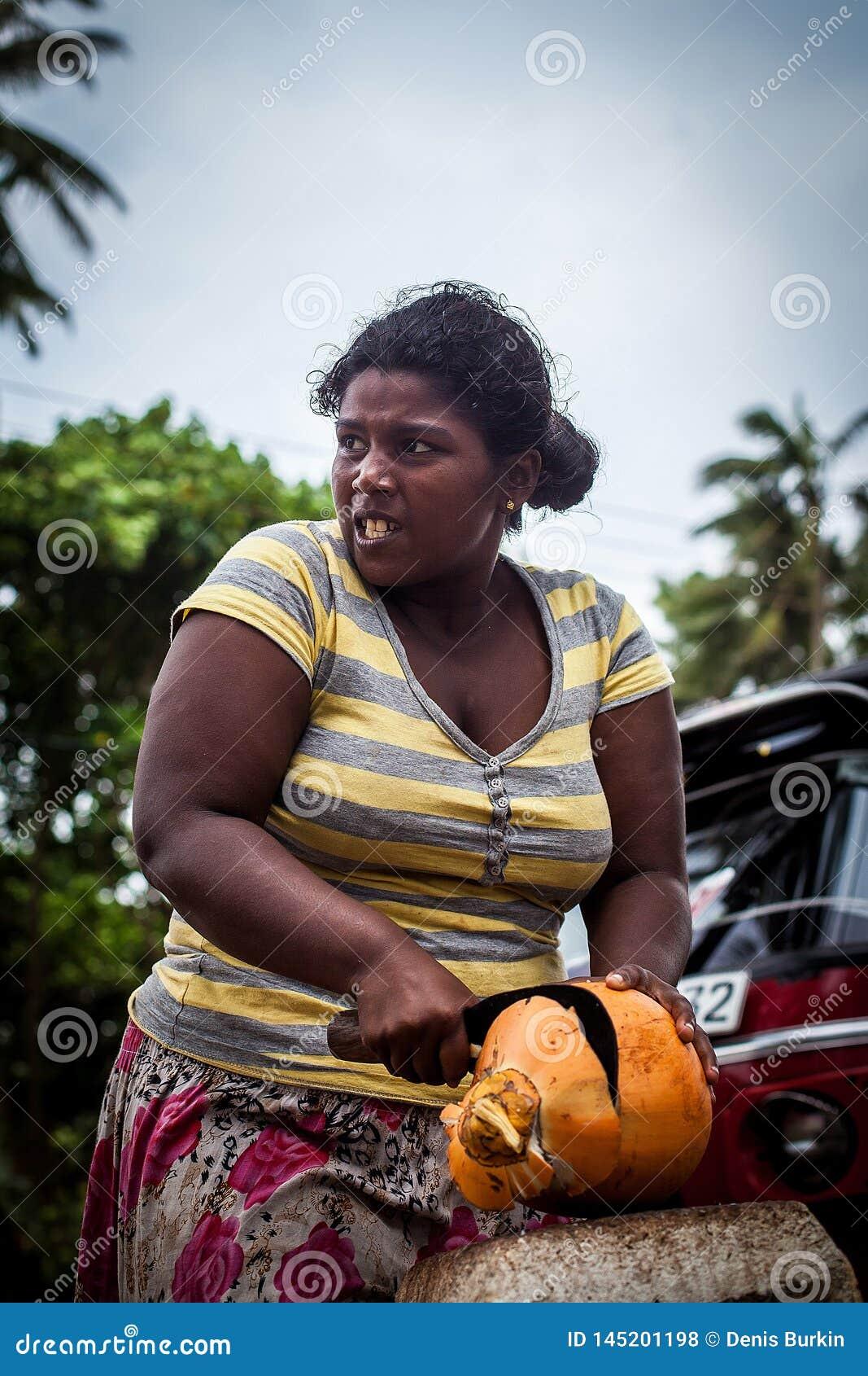 Uma mulher de pele escura corta um coco alaranjado com uma faca grande Mulheres duras de trabalho Mulher forte e digna que faz o