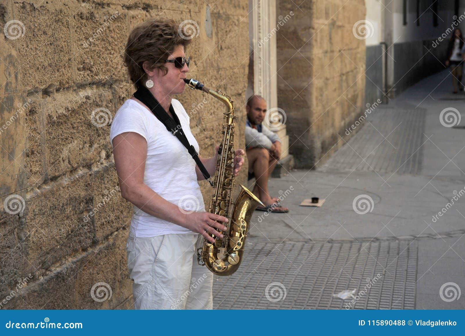 Uma mulher do desconhecido joga o saxofone na rua velha da cidade de Cadiz