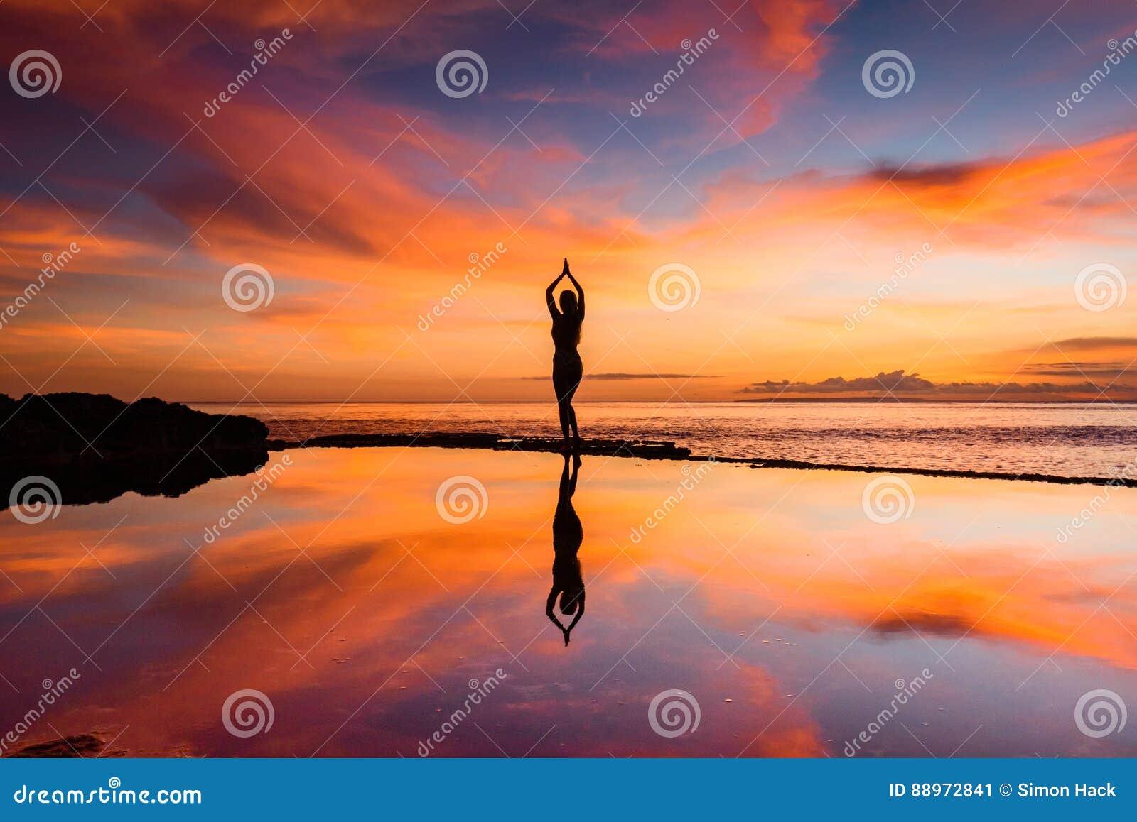 Uma mulher em uma pose da ioga mostrada em silhueta contra um por do sol com sua reflexão na água