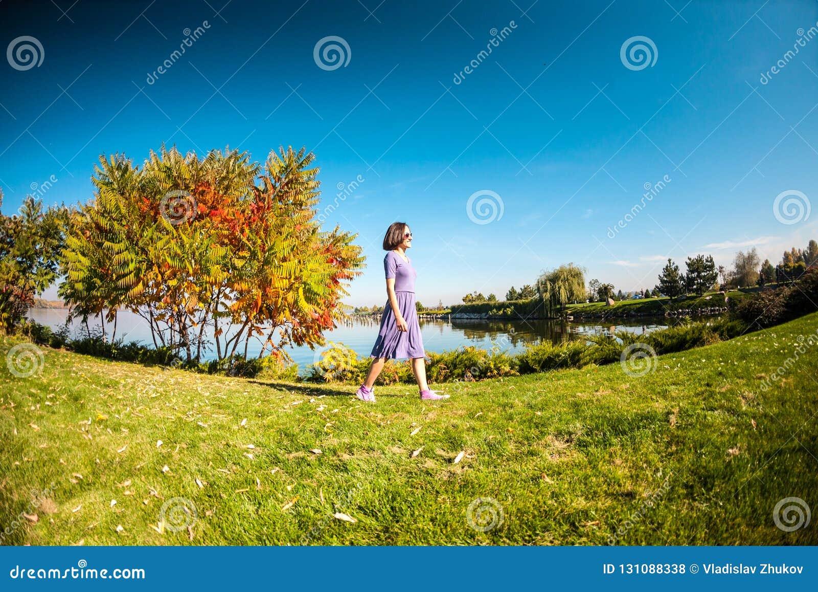 Uma mulher em um vestido está andando na grama
