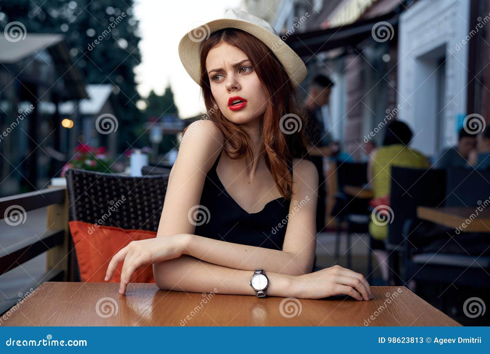 Uma mulher está sentando-se em um café no terraço