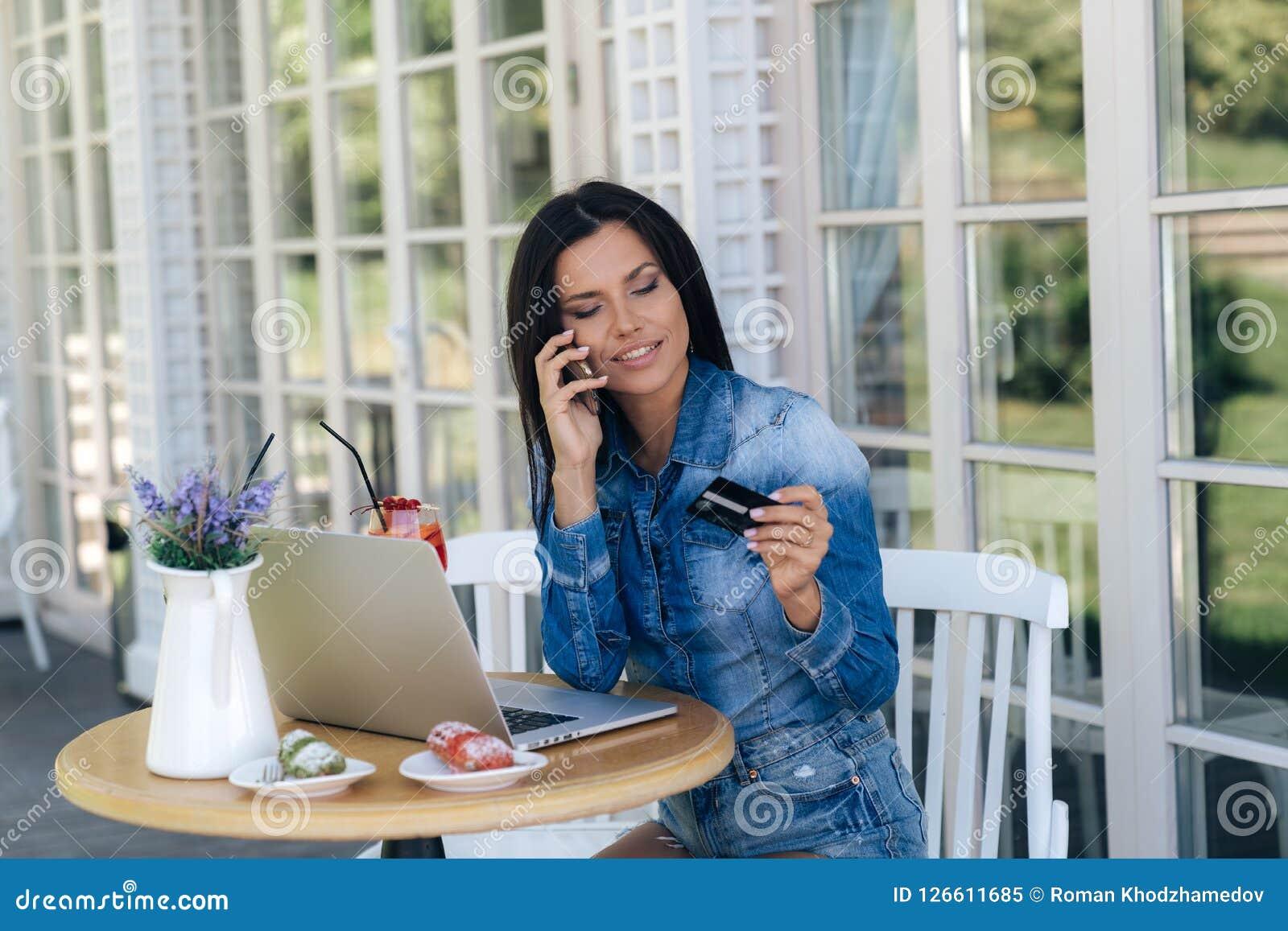 Uma mulher europeia nova bonita veste a roupa à moda, senta-se em uma tabela em um café, usa um portátil, bebe delicioso