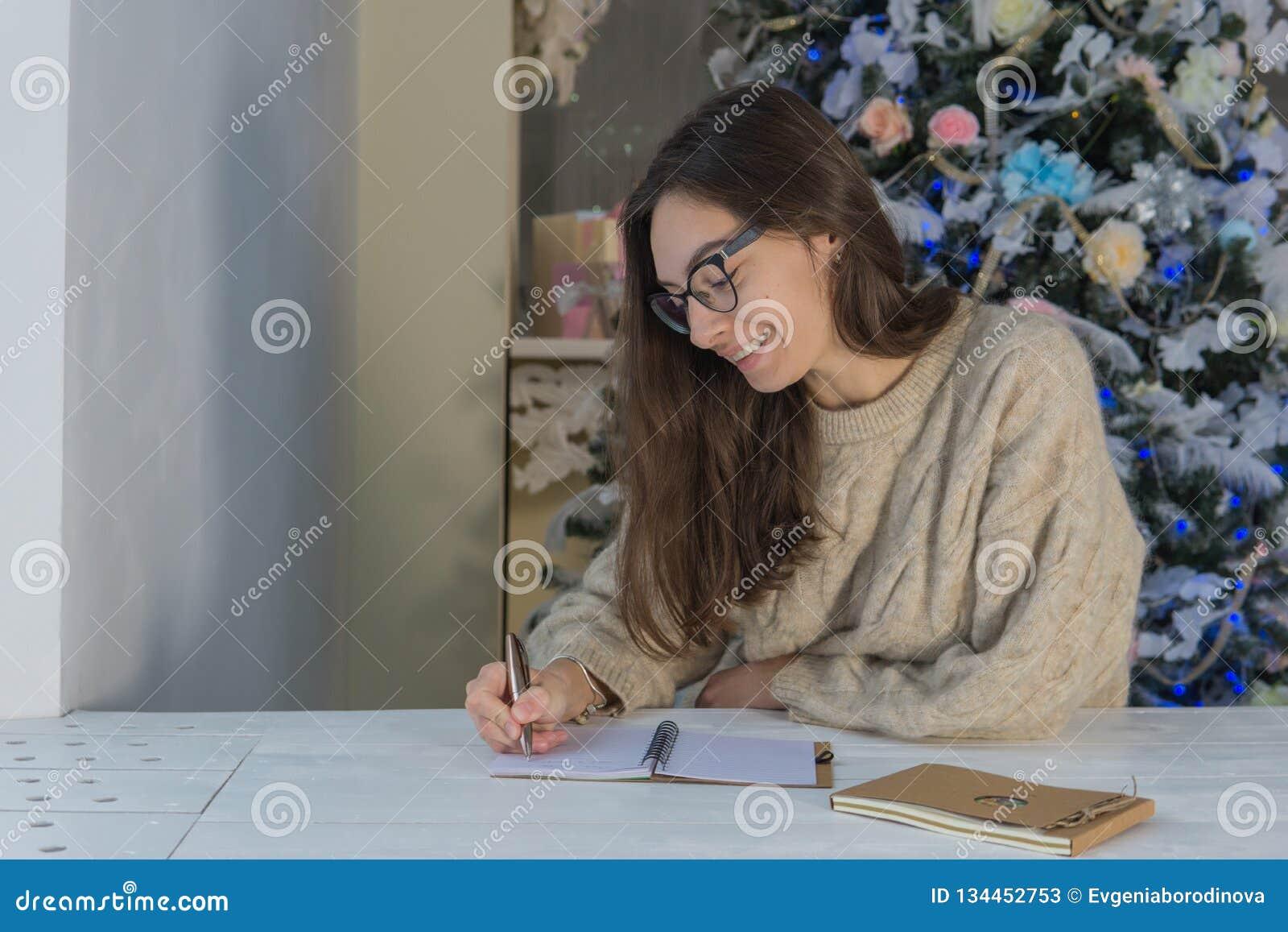 Uma mulher feliz nova redige uma lista de desejos do Natal ao lado da árvore de Natal