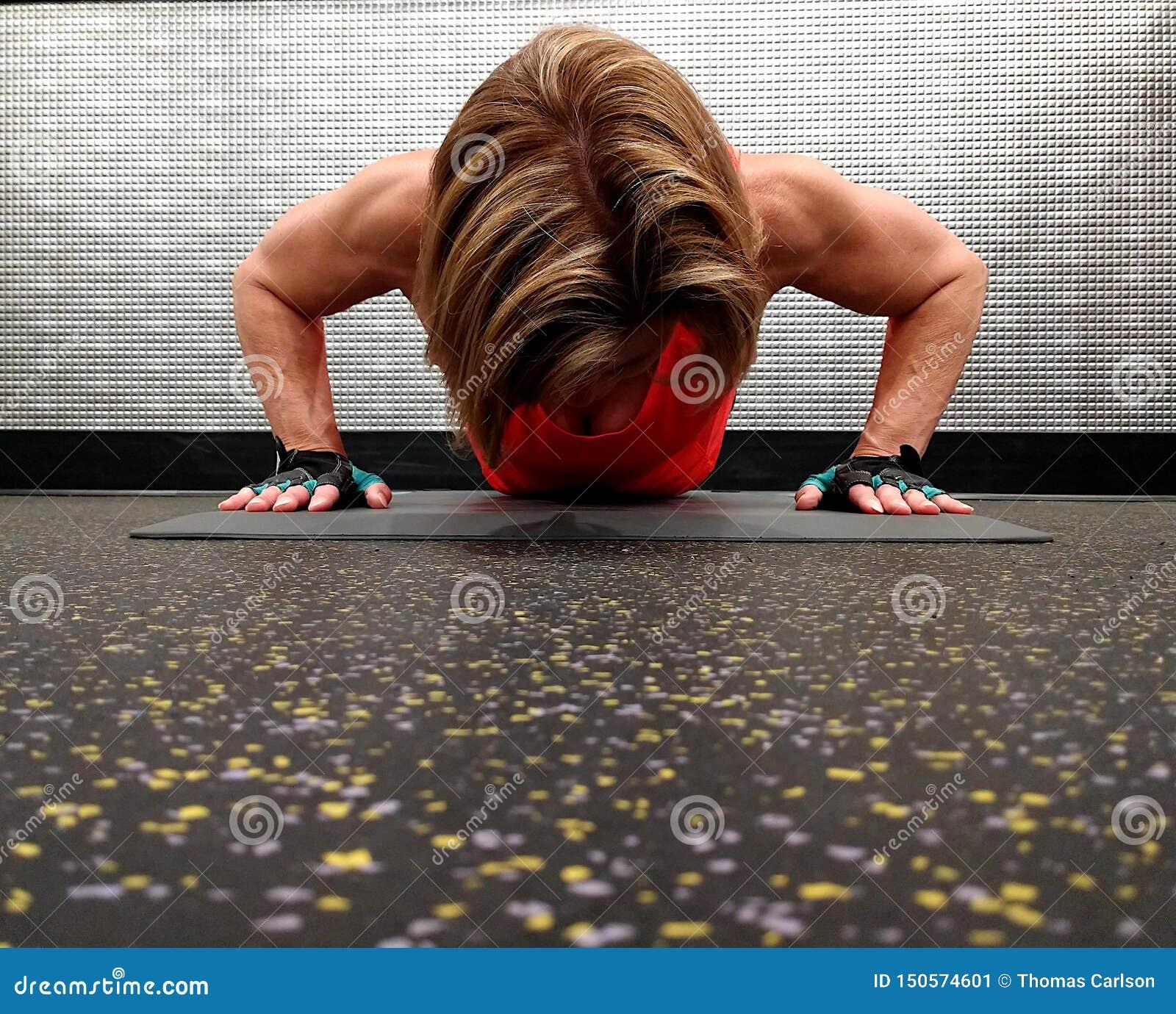 Uma mulher forte que exercita na posição do impulso acima