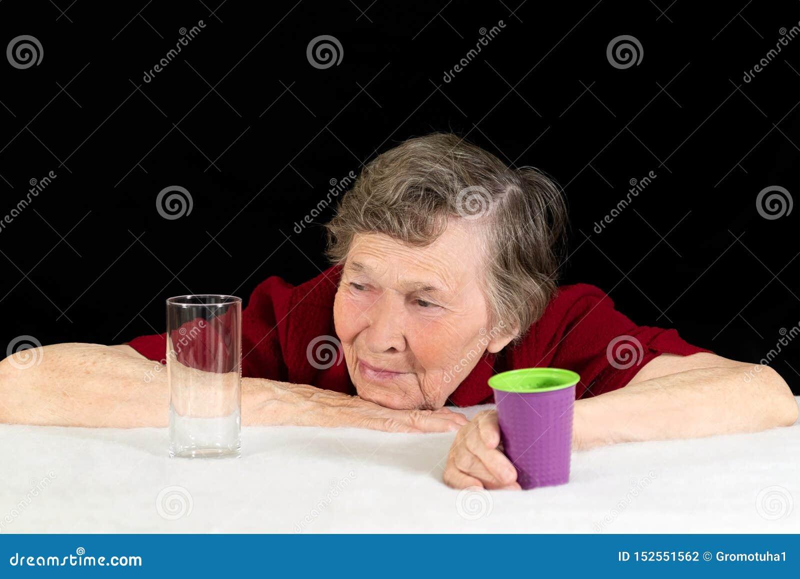 Uma mulher idosa com olhares cinzentos do cabelo nos produtos vidreiros com aprovação e um sorriso, empurrando o copo plástico af