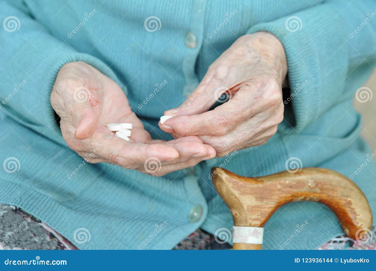 Uma mulher idosa com um bastão que guarda um comprimido na rua 90 anos saúde doença e cuidados médicos do conceito