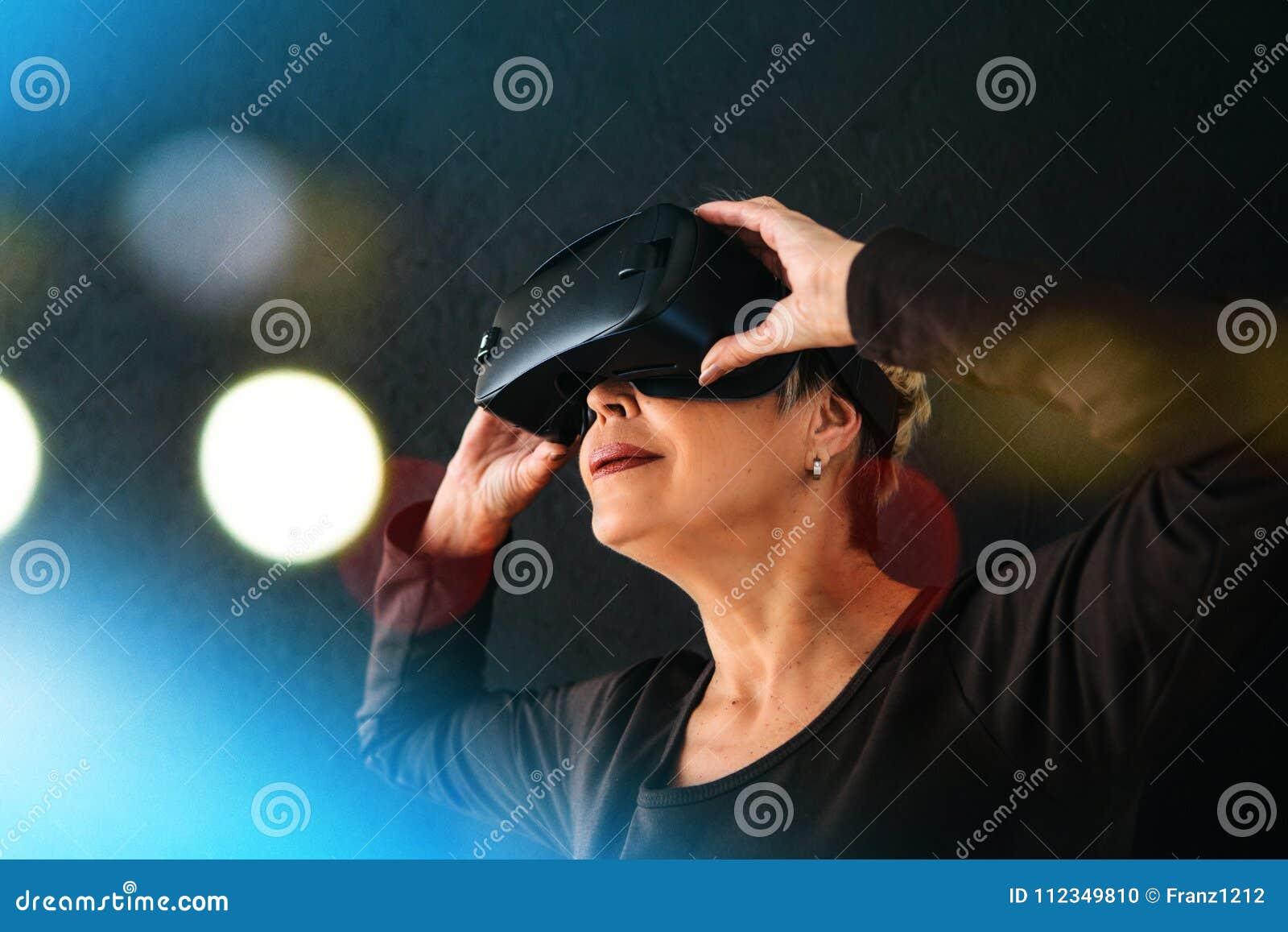 Uma mulher idosa em vidros da realidade virtual Uma pessoa idosa que usa a tecnologia moderna