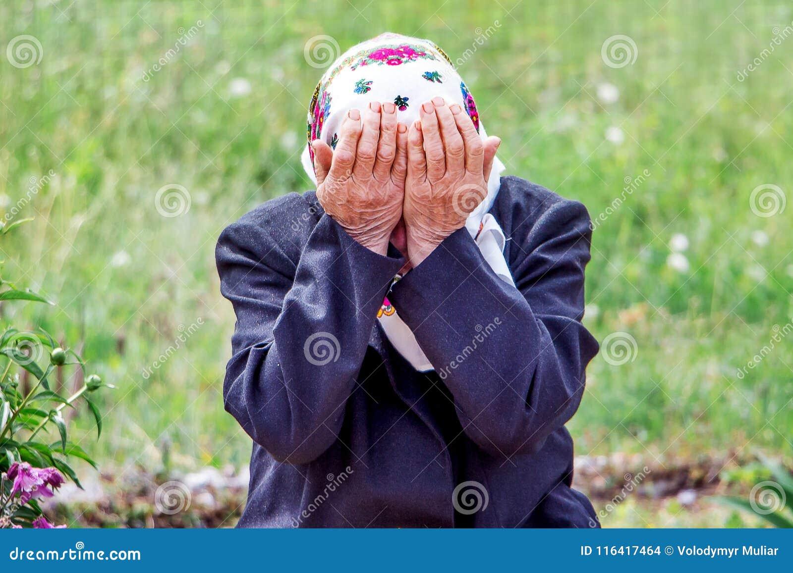 Uma mulher idosa grita, cobrindo sua cara com suas mãos Símbolo