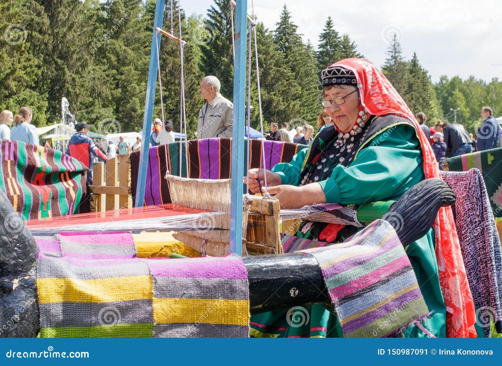 Uma mulher idosa na roupa Bashkir é assentada em um oom de madeira velho e tece um tapete Feriado nacional Sabantuy no parque da