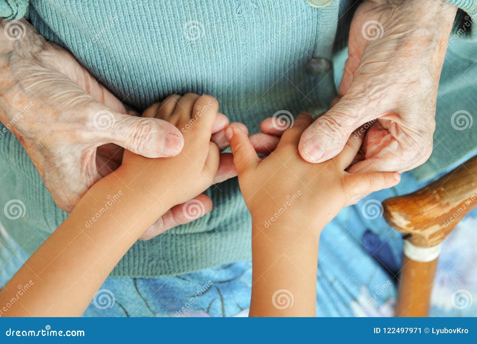 Uma mulher idosa que guarda as mãos do ` s das crianças, um bastão de madeira na rua bisavó e grande-neto