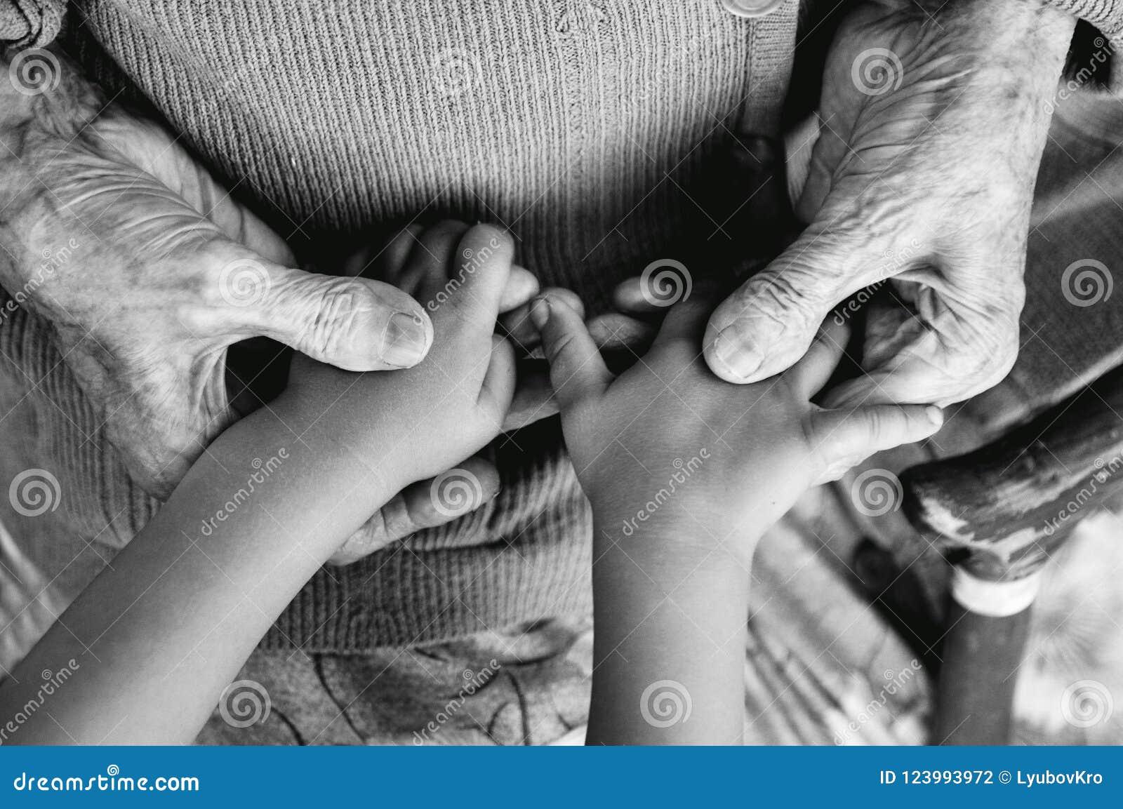 Uma mulher idosa que guarda as mãos do ` s das crianças, um bastão de madeira na rua bisavó e grande-neto Phot preto e branco