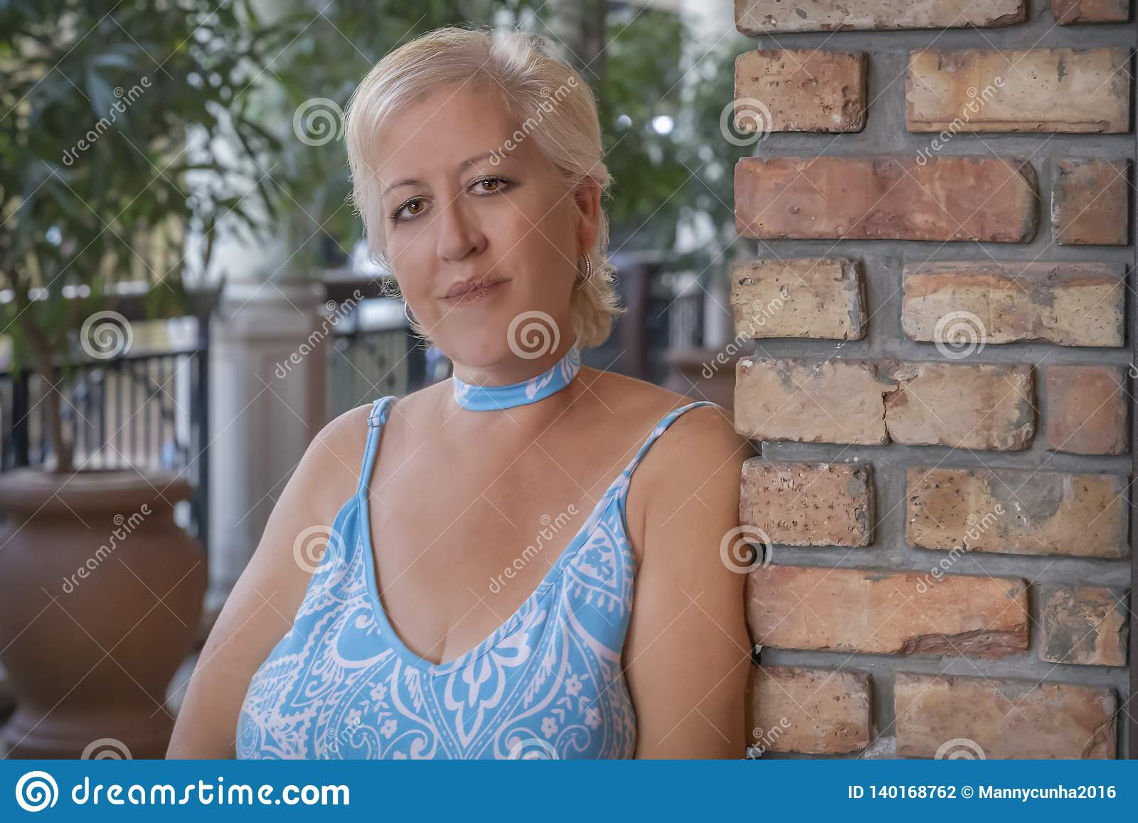 Uma mulher loura madura inclina-se em uma parede de tijolo que olha a câmera com um sorriso