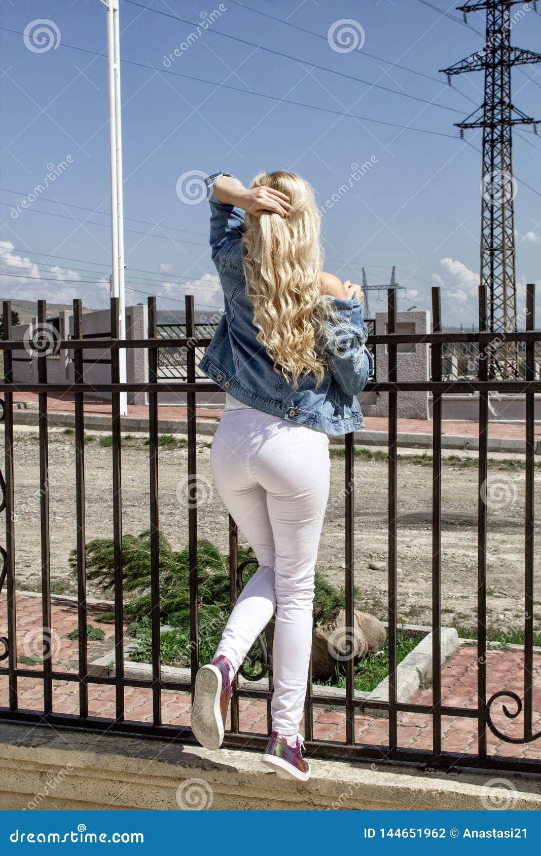 Uma mulher loura nova bonita está estando com sua parte traseira contra a cerca