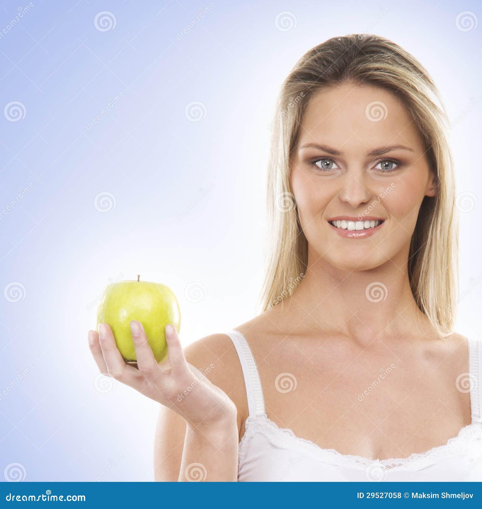 Uma mulher loura nova que guardara uma maçã verde