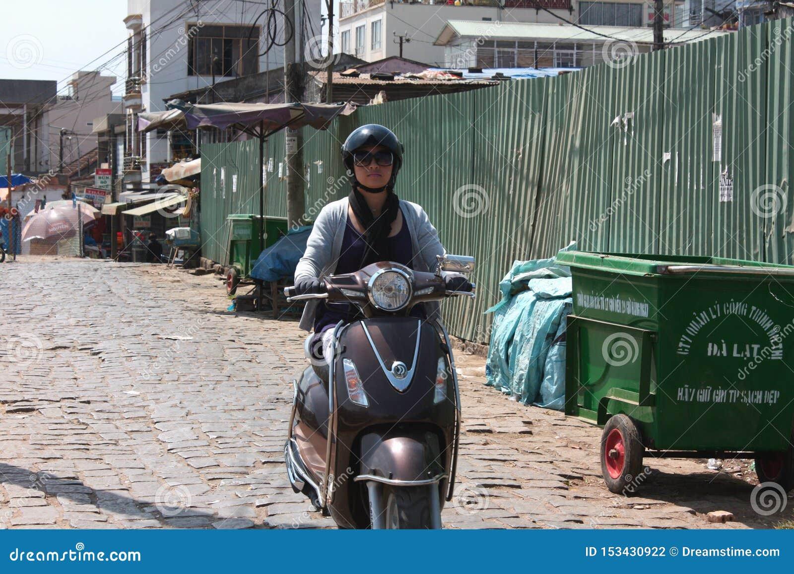 Uma mulher monta uma motocicleta Vietname, motobike de Dalat
