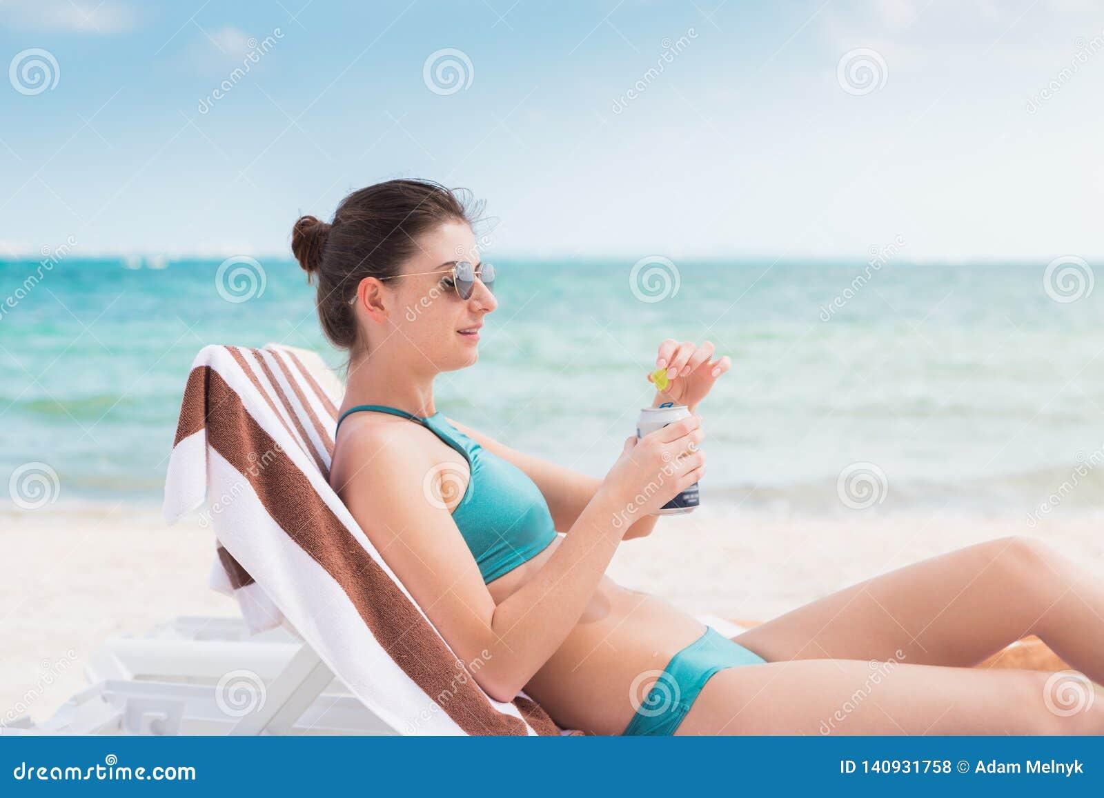 Uma mulher moreno nova atrativa em uma cadeira de praia que bebe uma cerveja fria em uma praia em México