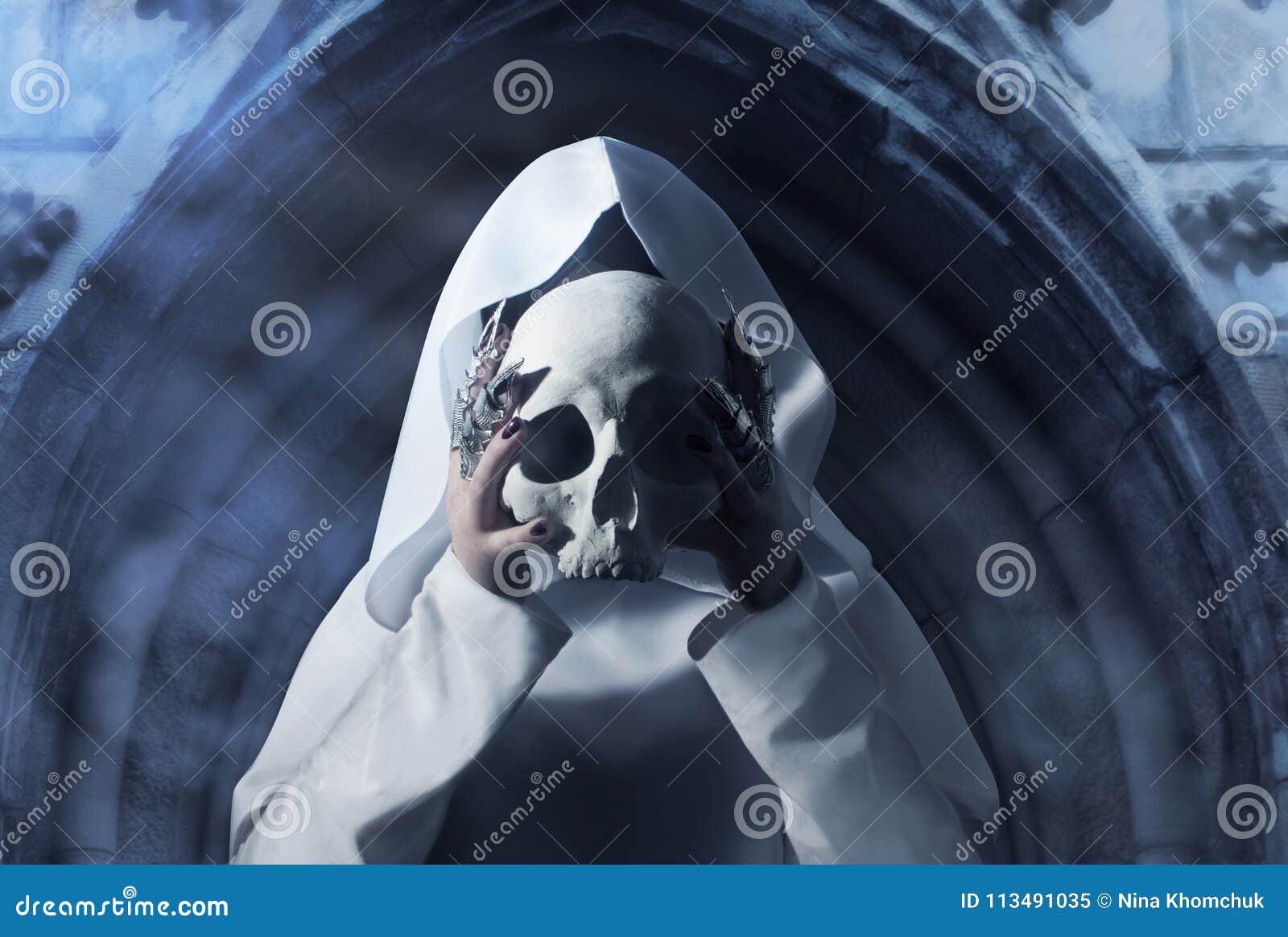 Uma mulher no casaco com um crânio humano