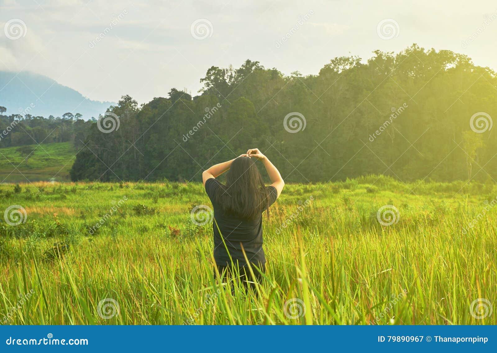 Uma mulher no pano preto está estando no campo de grama