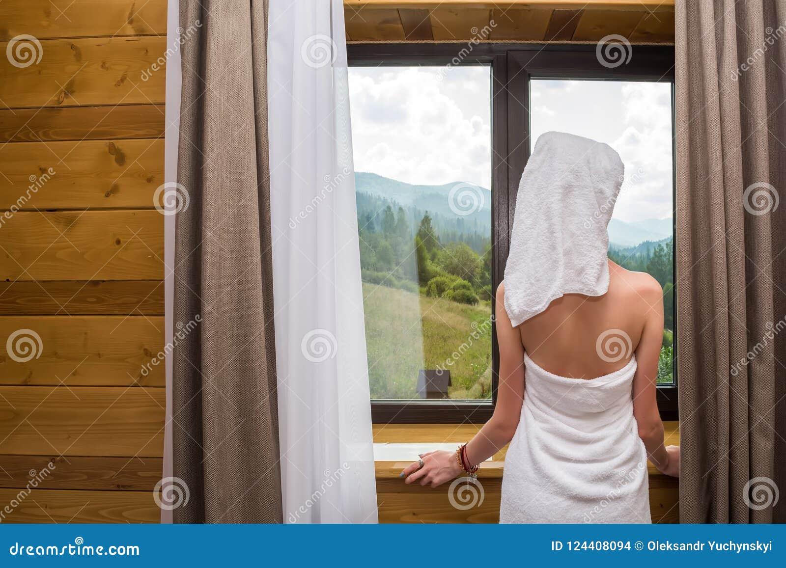 Uma mulher nova, bonita,  sexy , depois que um chuveiro, suportes envolvidos em uma toalha perto da janela no hotel com uma vista