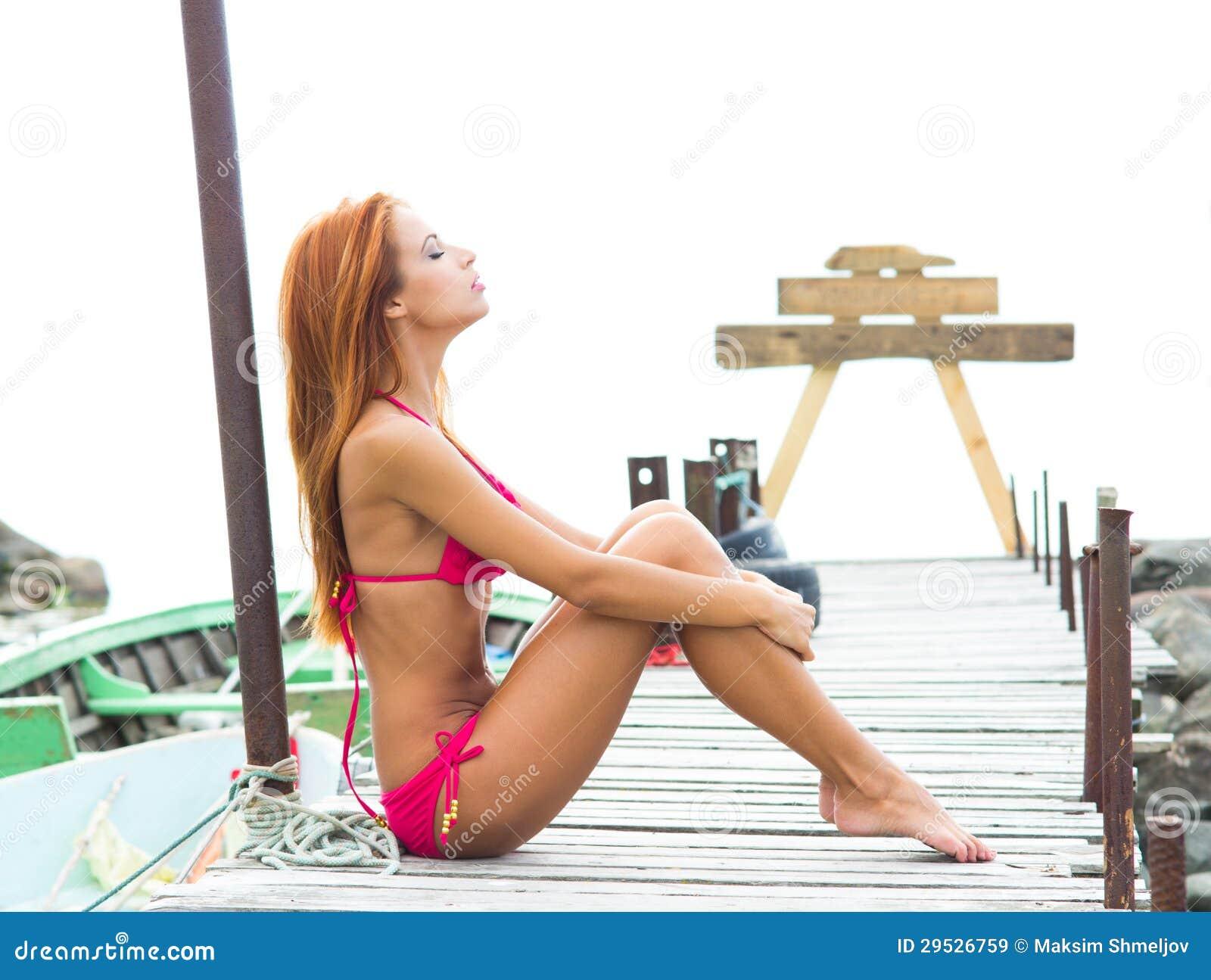 Uma mulher nova do redhead que coloca em um roupa de banho cor-de-rosa